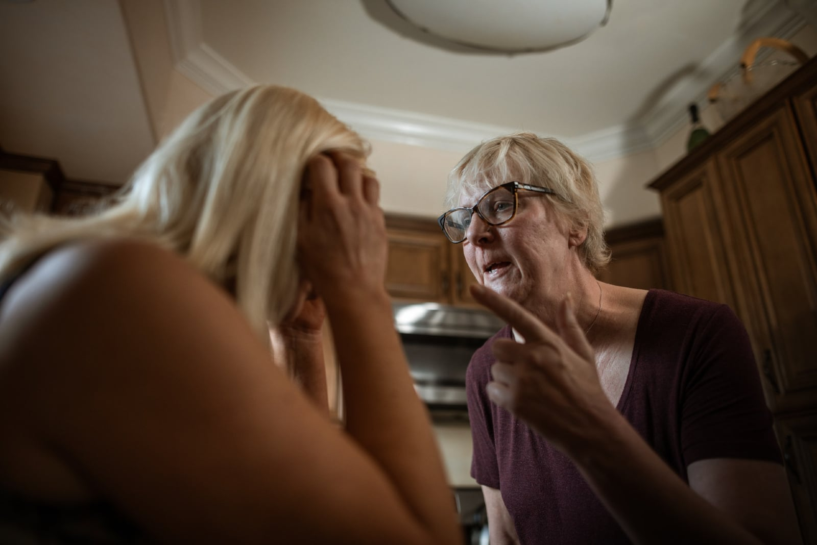 woman with eyeglasses talking to woman indoor