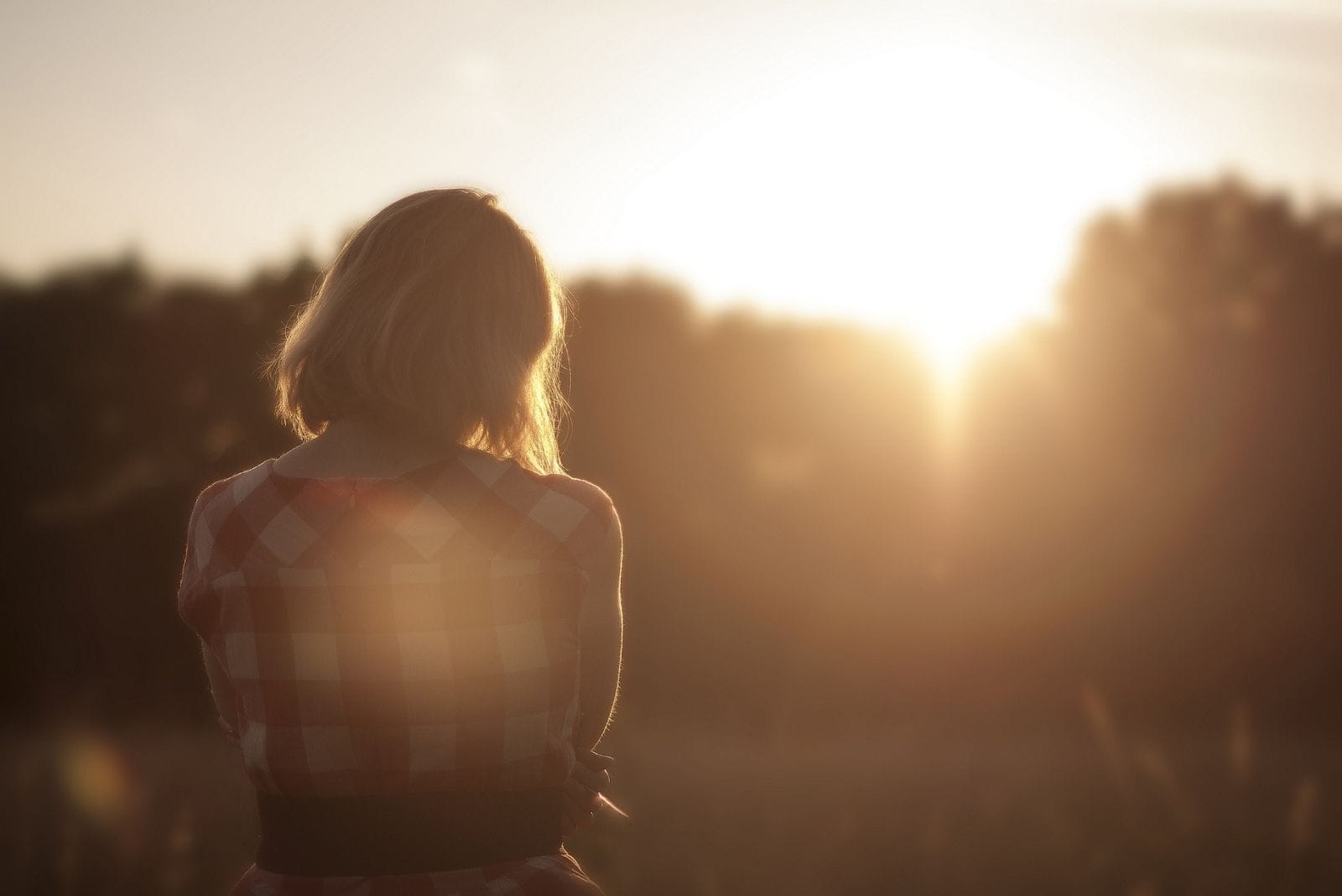 woman thinking and standing in the meadow facing the setting sun