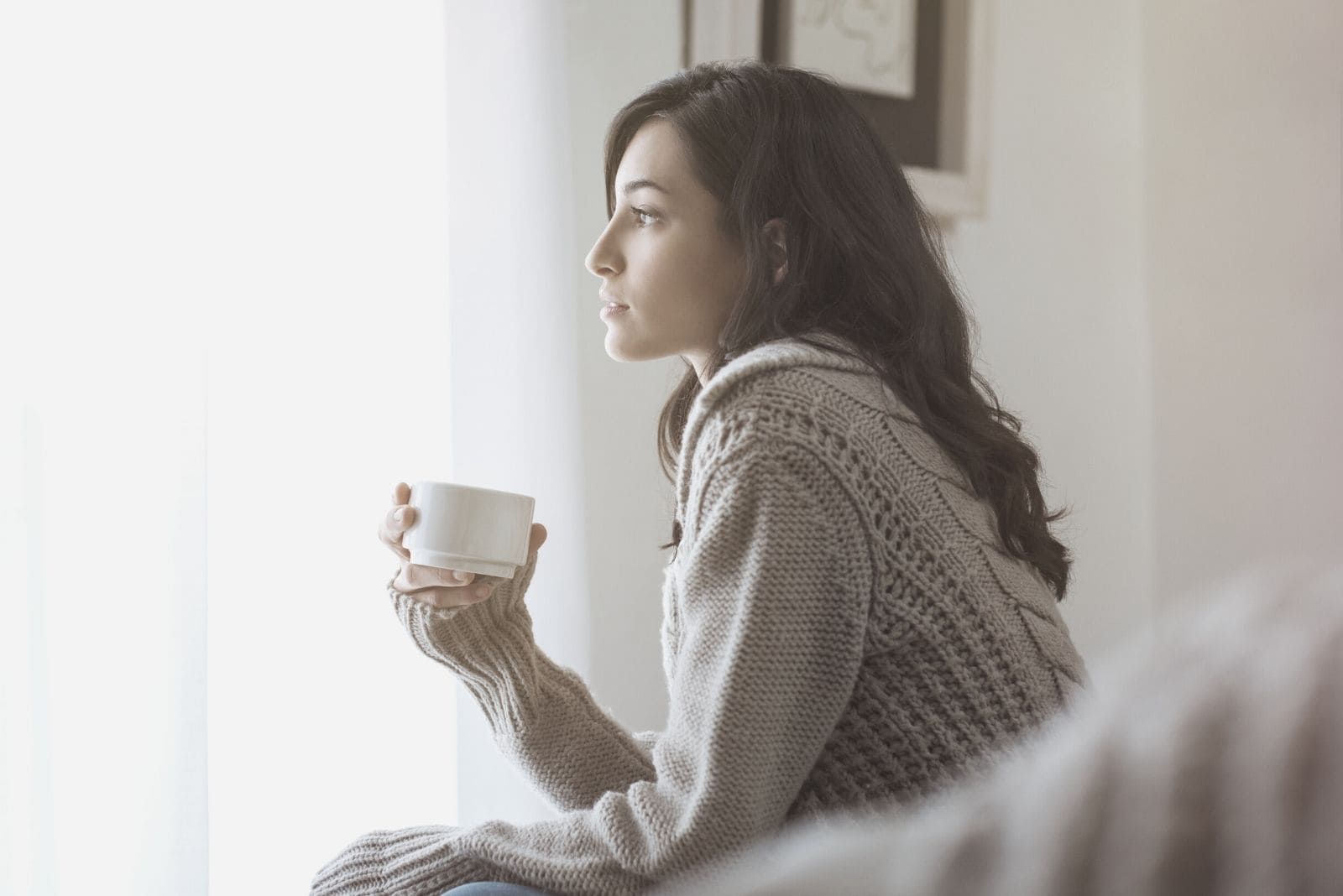 woman thinking at home drinking from a cup sitting on sofa looking far