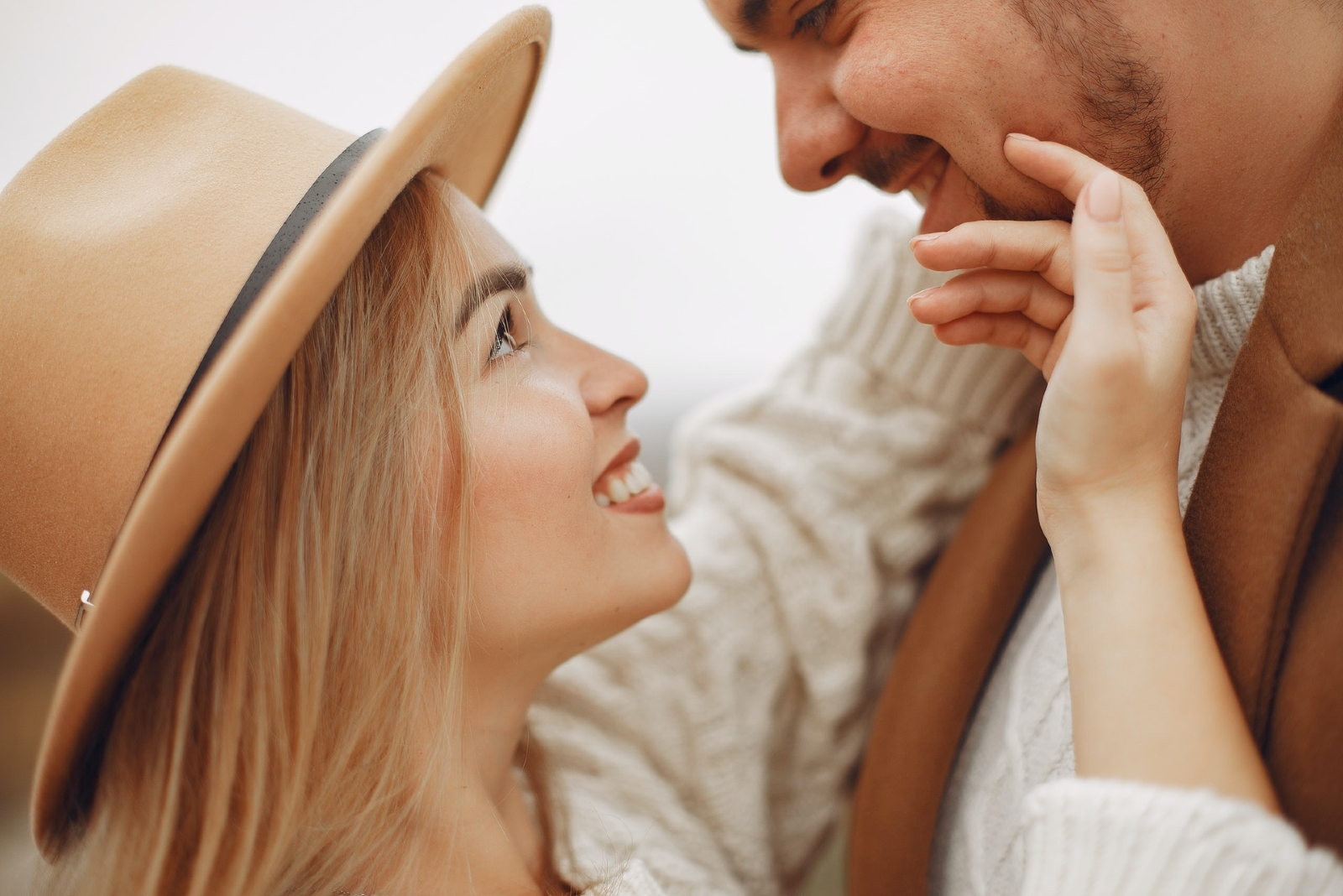 woman with brown hat touching man's face