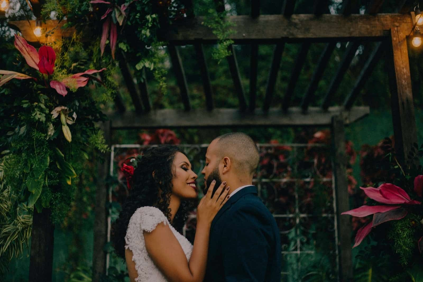 bride touching groom's face while standing near plants