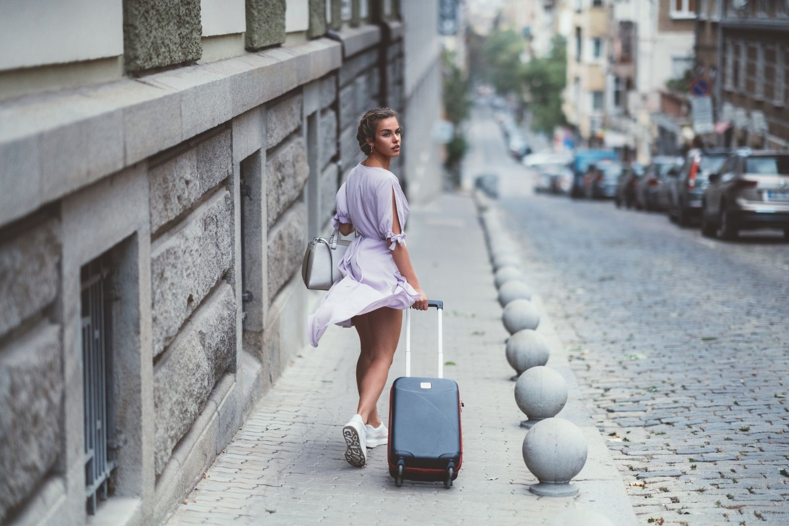 woman travelling alone looking back carrying luggage along the side walk