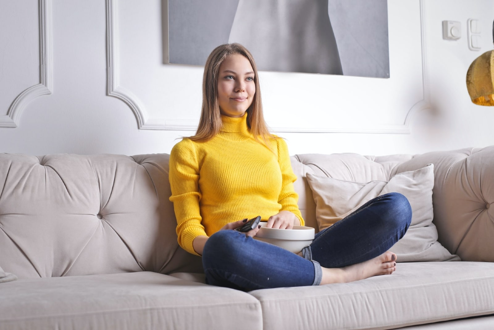 woman watching tv while sitting on sofa