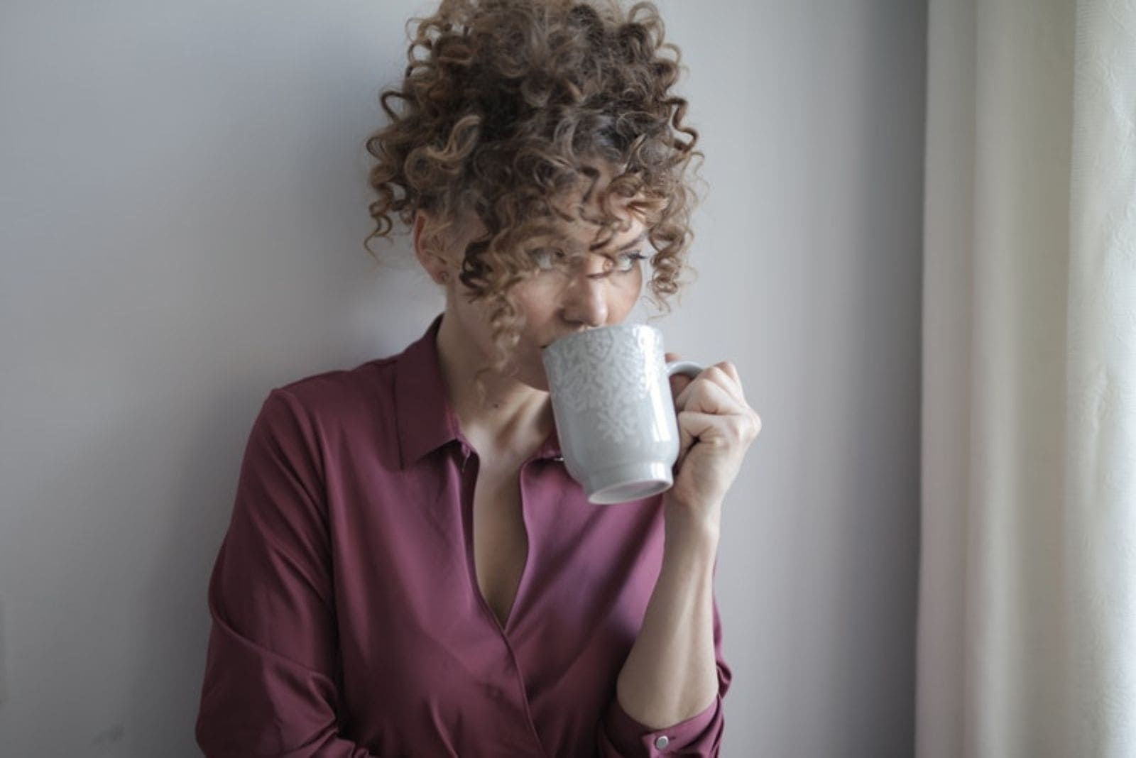 woman with curly hair leaning on the room's wall looking away and drinking from a mug