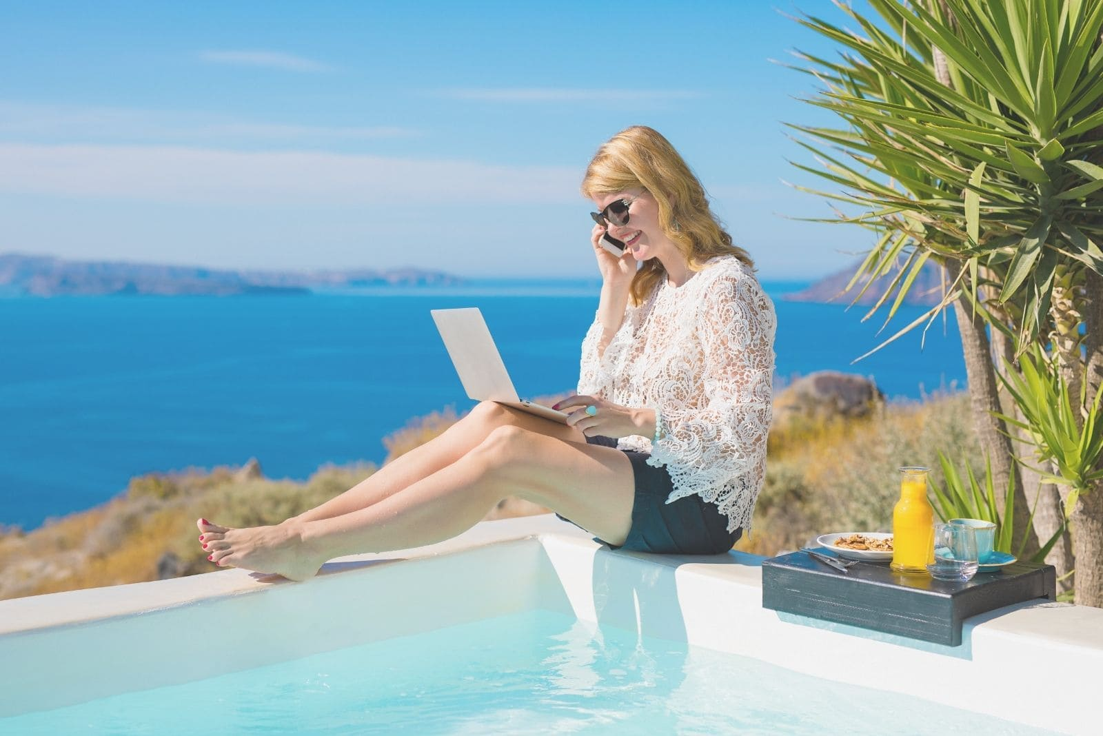 woman working on vacation sitting beside the pool with food and laptop