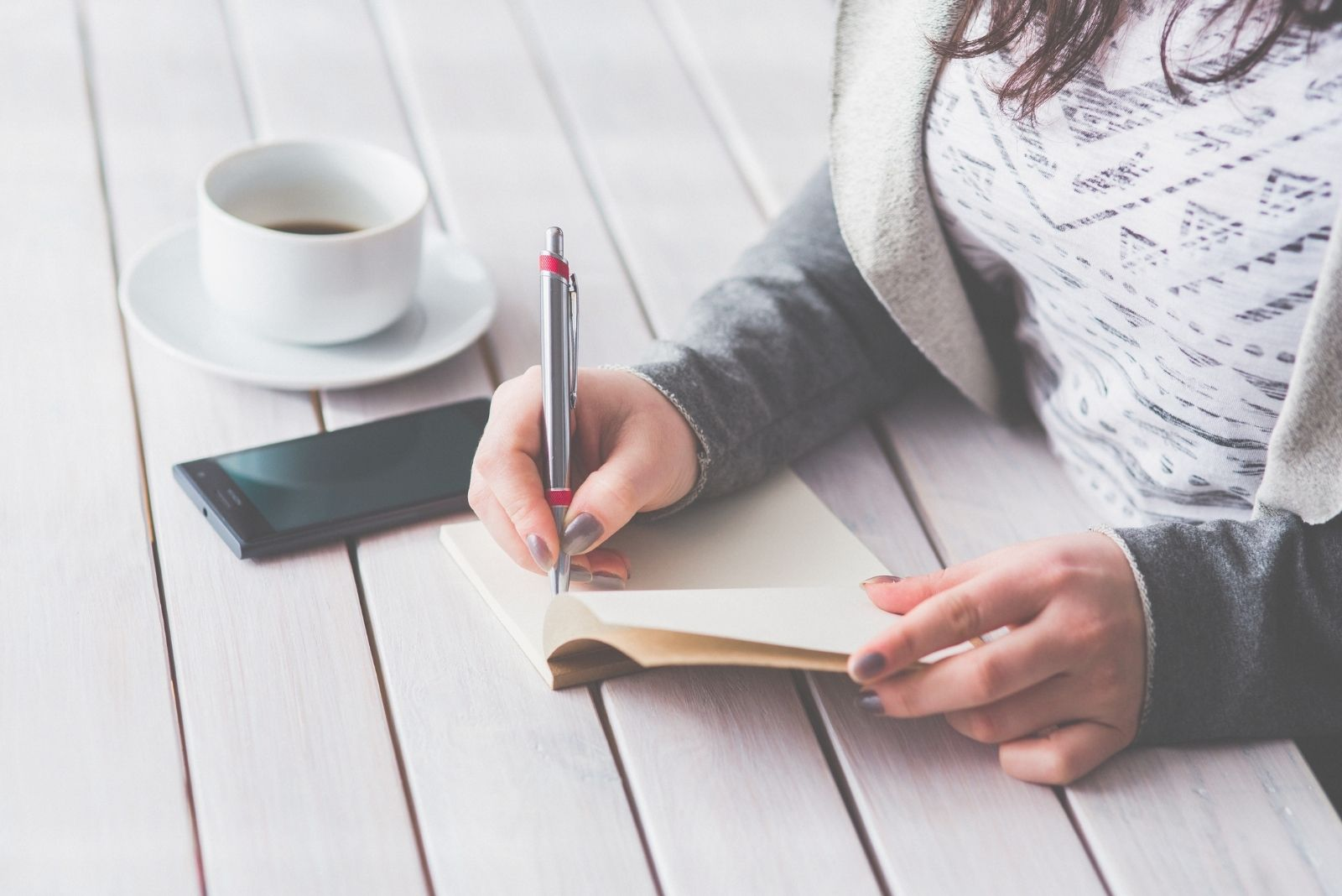 woman writing on her journal on a wooden table with phone and coffee on the table in cropped image
