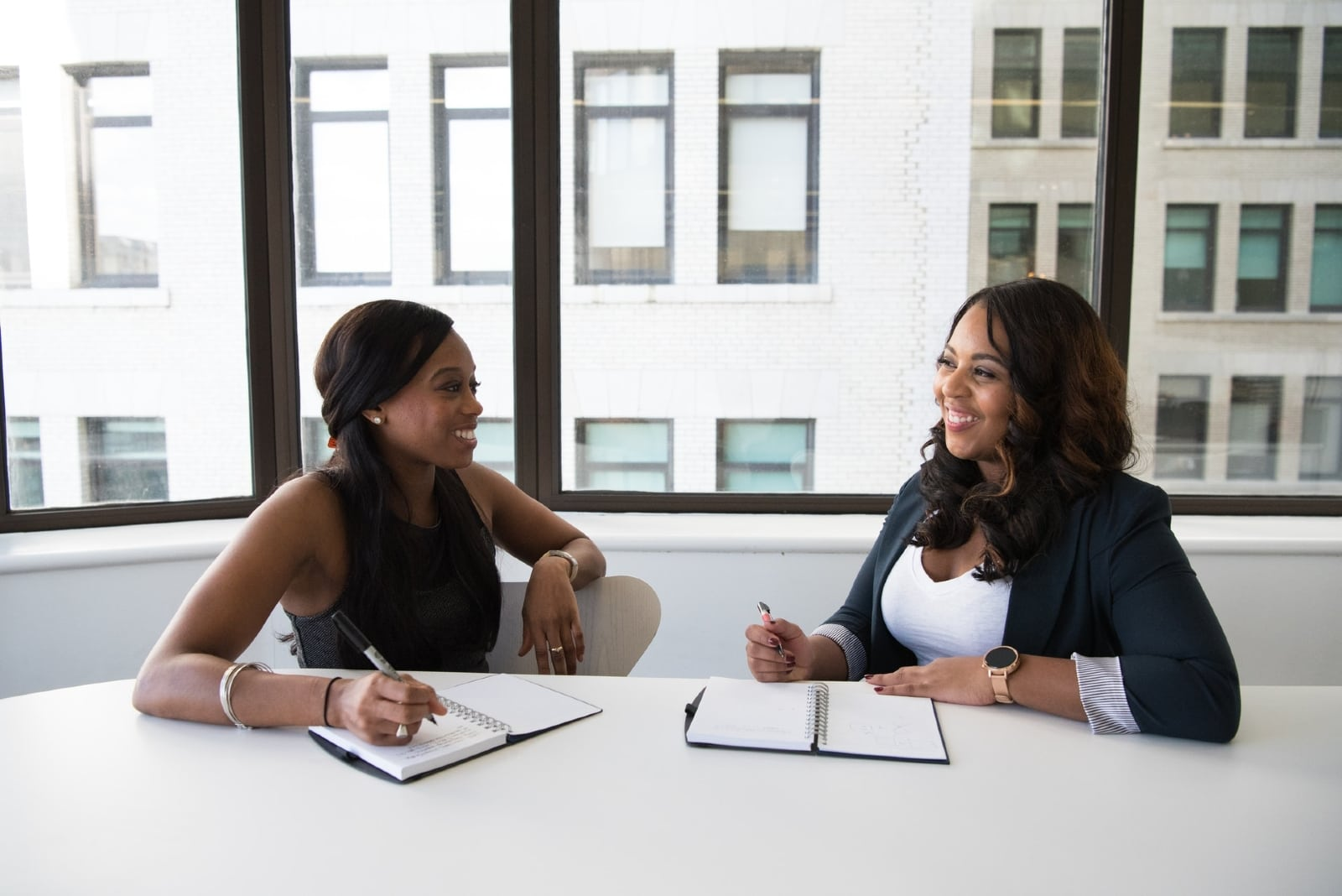 two women talking while sitting at table in office