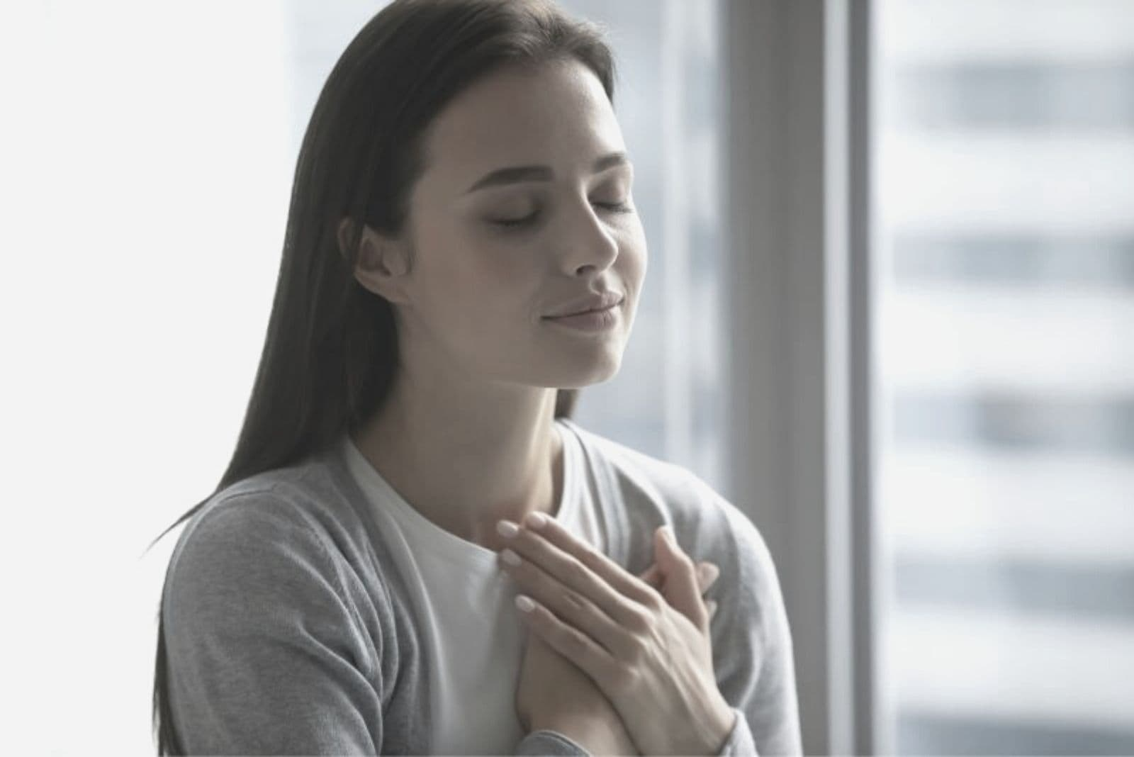 young beautiful woman closing her eyes and putting her hands close to her chest standing indoors