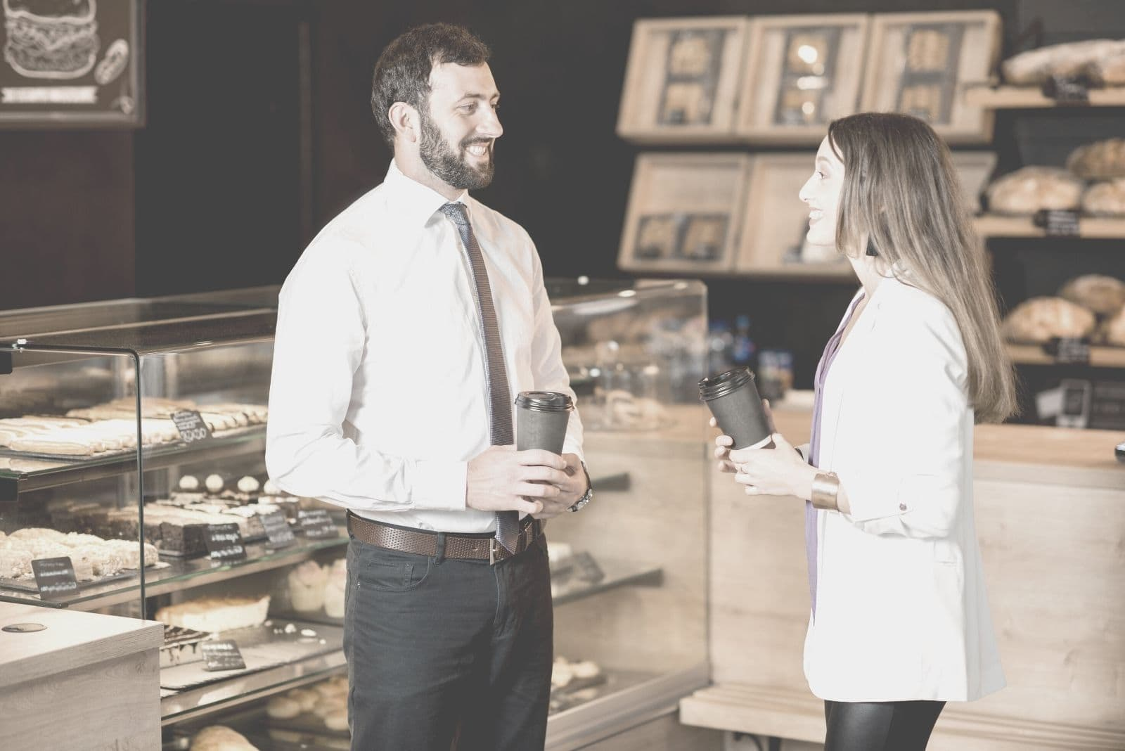 young businessman and woman talking while buying coffee inside a cafe