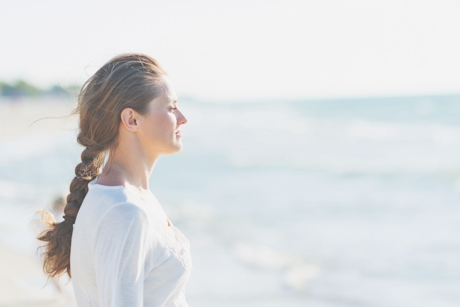 young calm woman standing near the sea and closing eyes