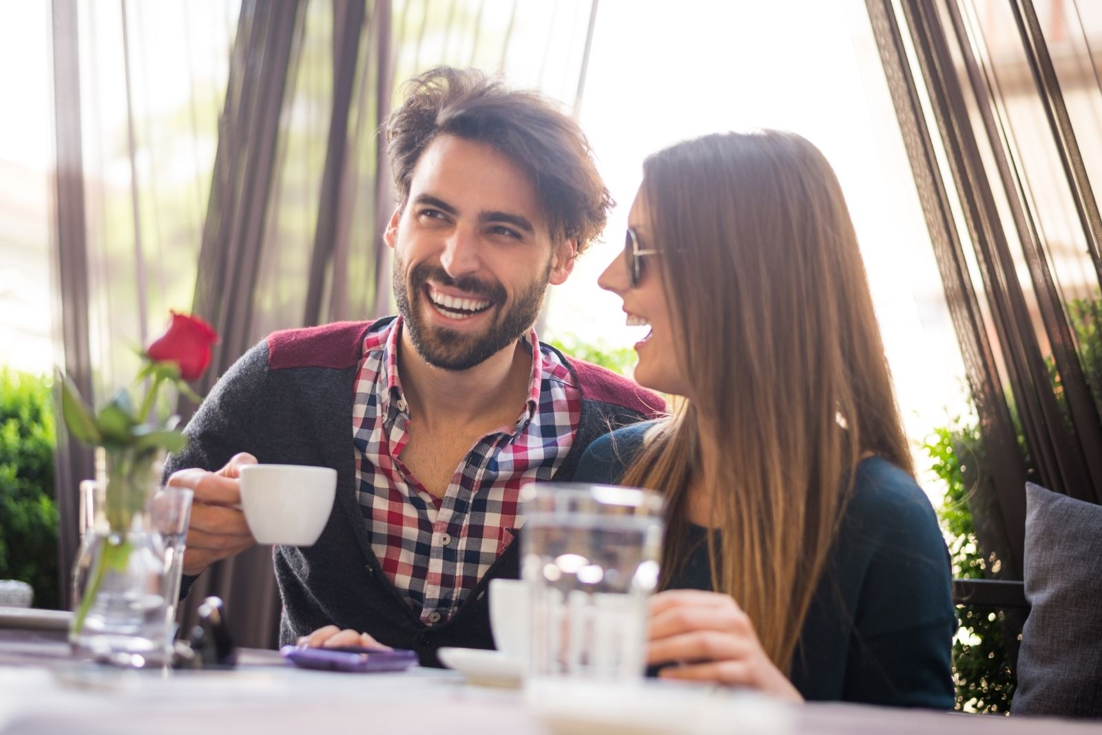 young couple dating in a cafe smiling and laughing in an outdoor cafe