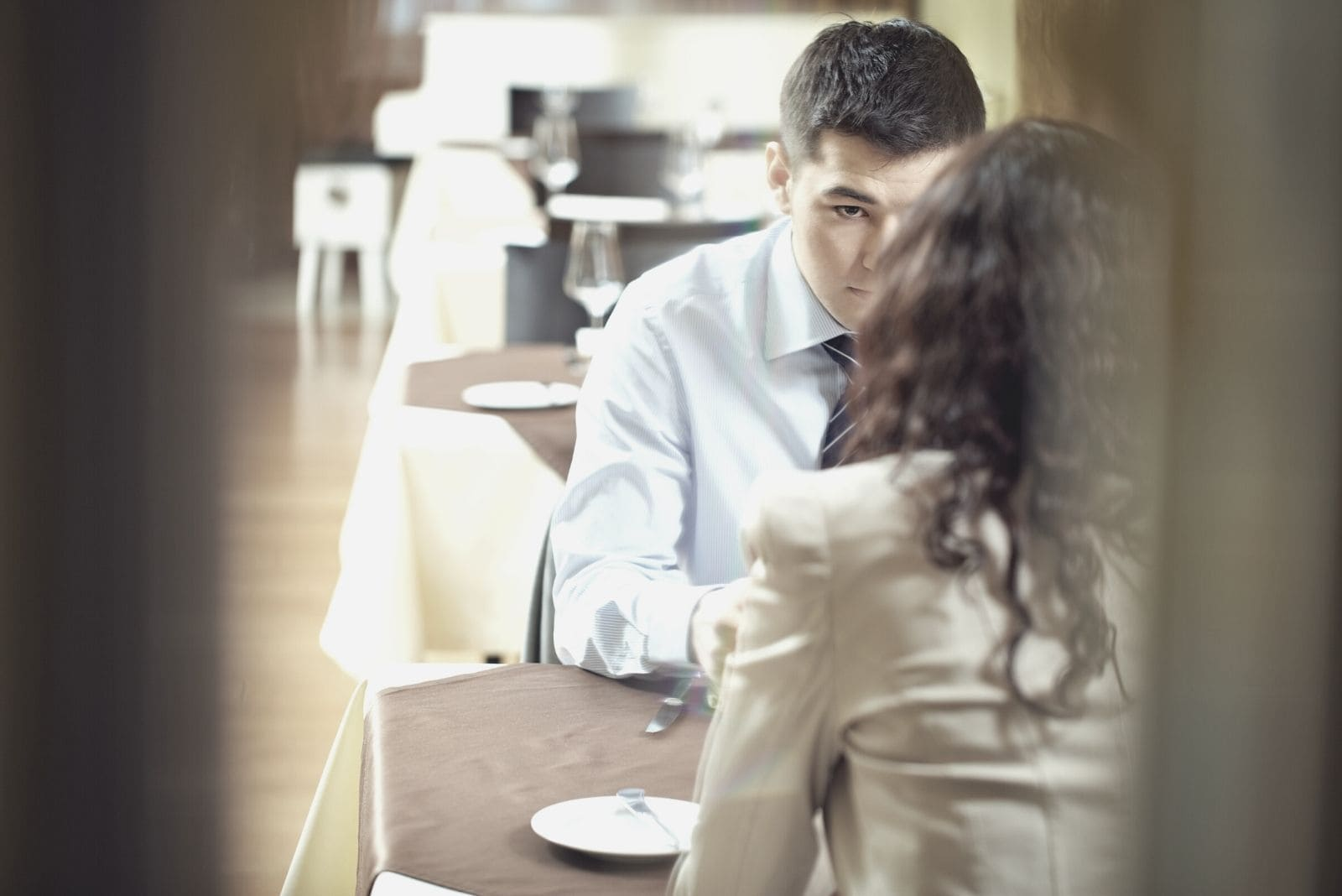 young couple sitting inside the restaurant talking seriously