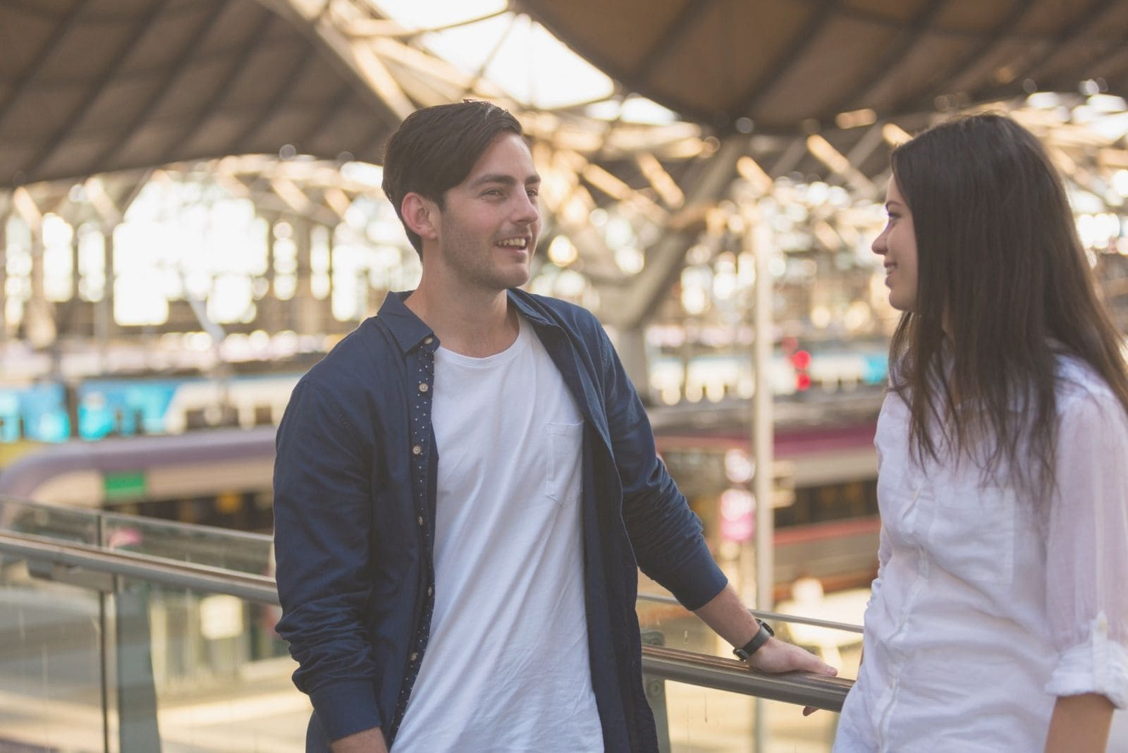 young couple standing at the train station standing wearing white top