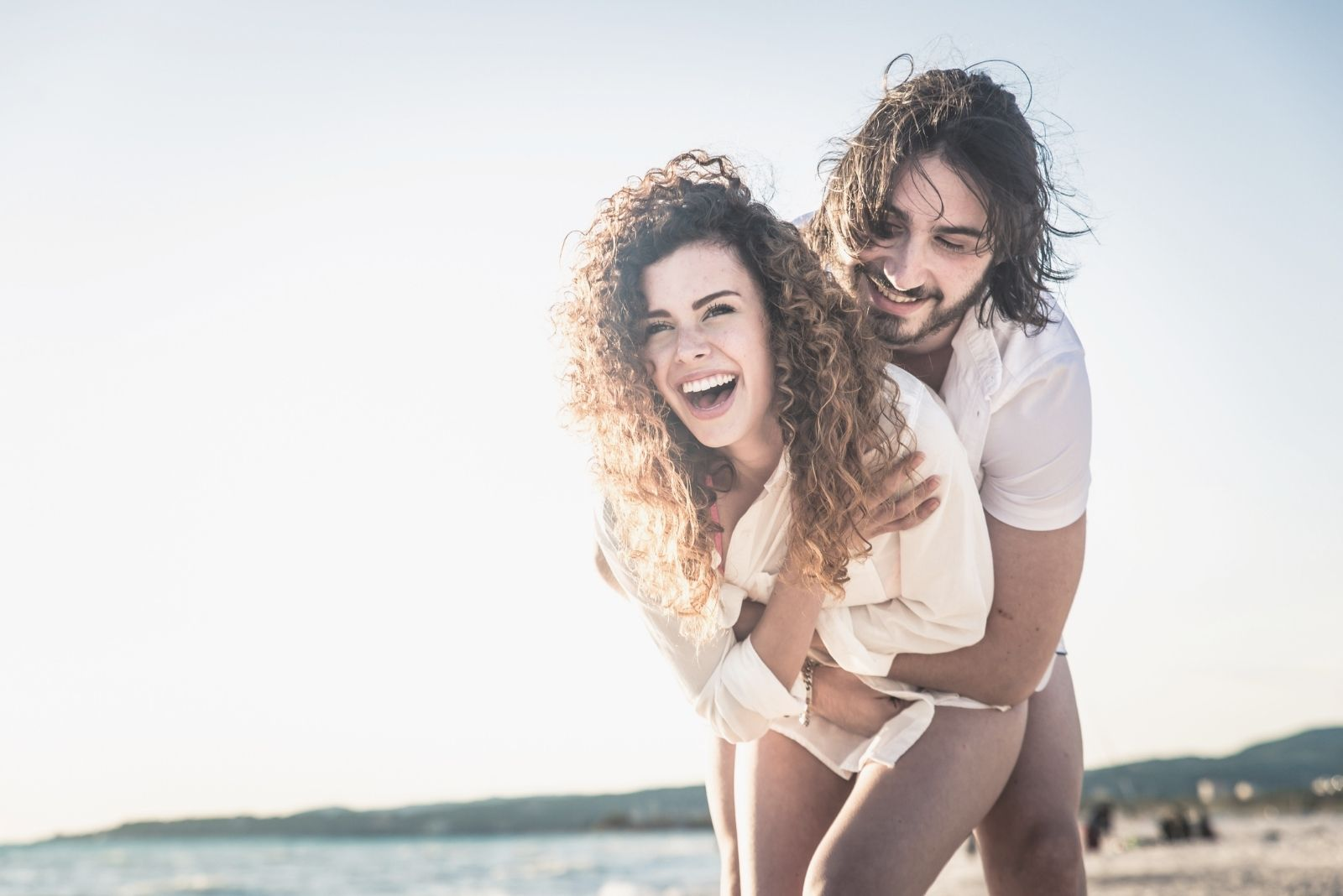 young happy couple hugging and laughing in the beach