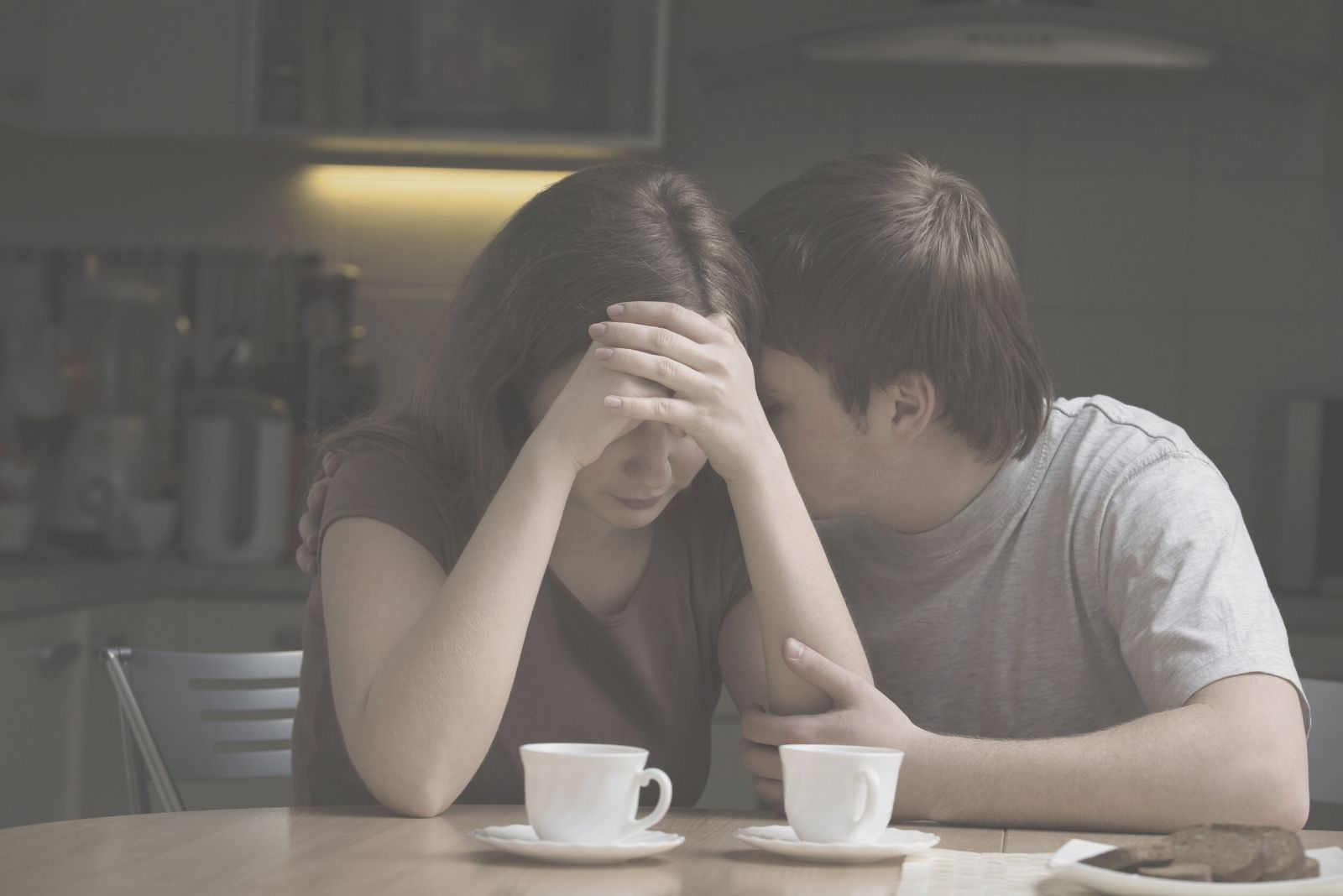 young man consoling woman with a problem in the dining room