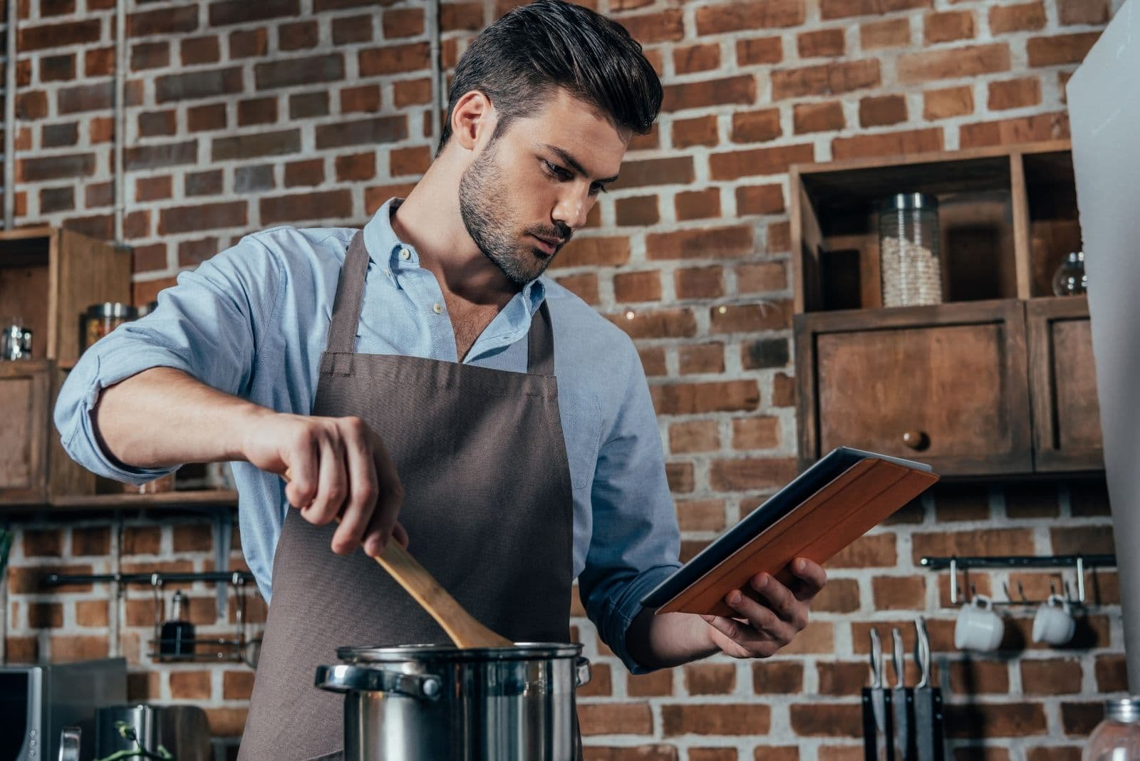 young man cooking in the kitchen looking at the cookbook while stirring