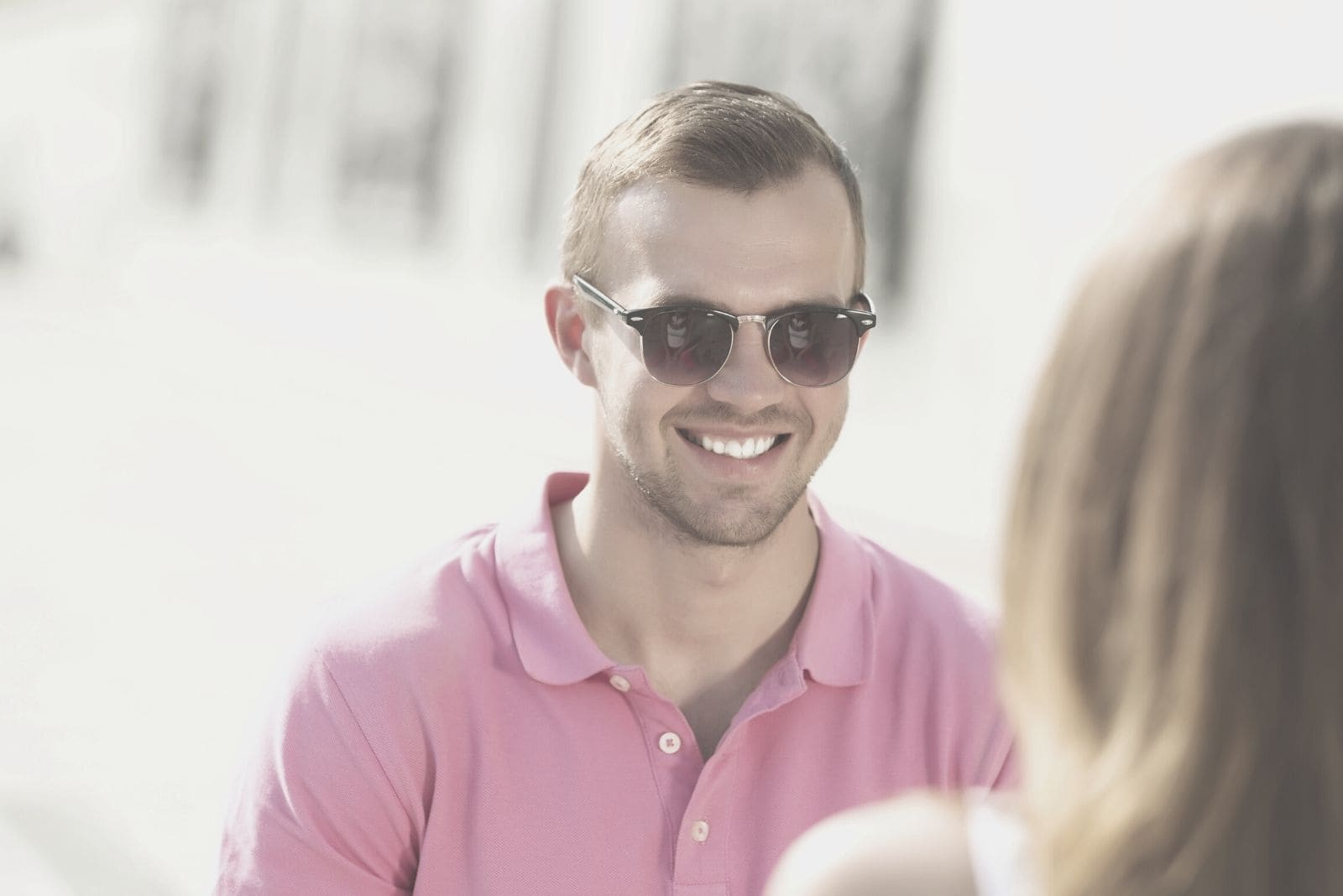 young man in pink top wearing sunglasses smiling at a woman outdoors
