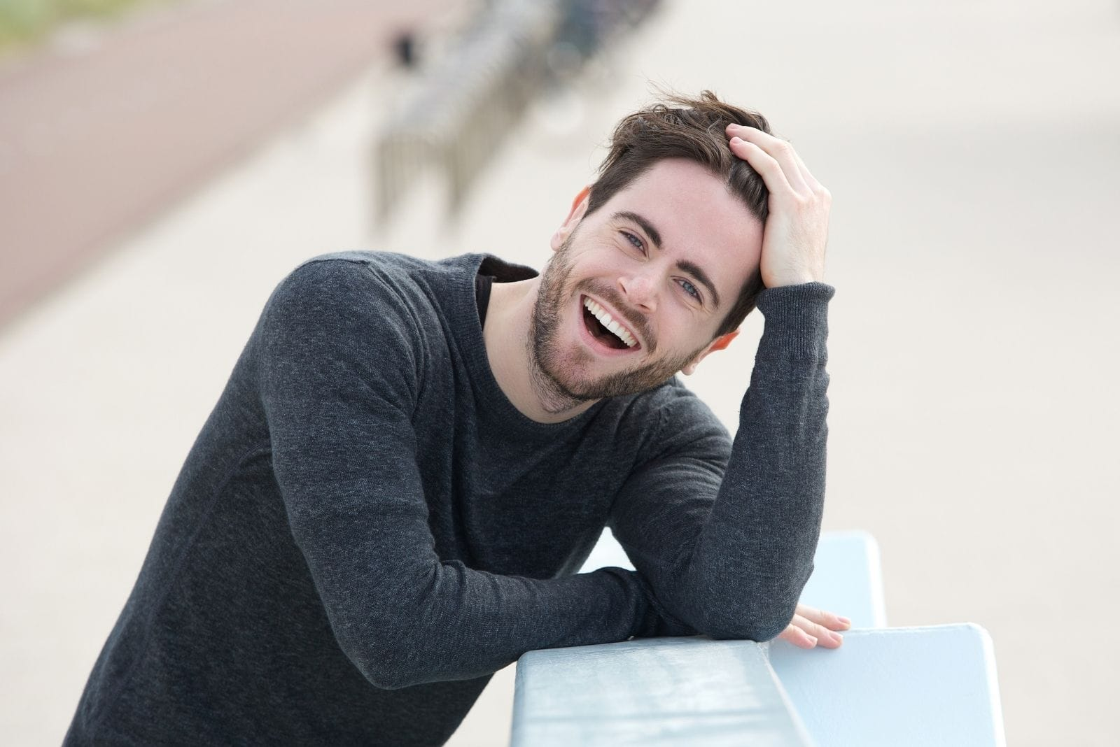 young man laughing holding his head leaning on the ledge outdoors