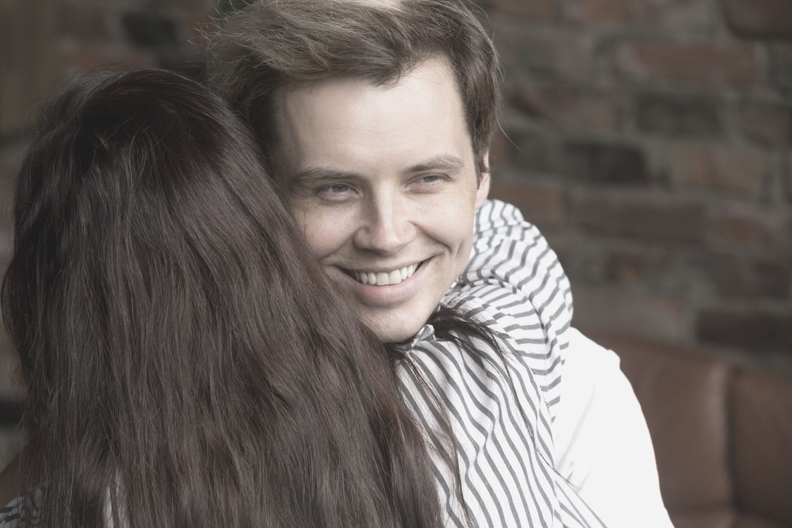 young sly liar man happily smiling embraced by a woman