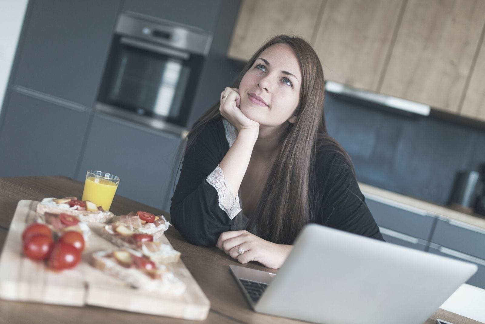 young woman daydreaming in the kitchen with food on the side while working on laptop