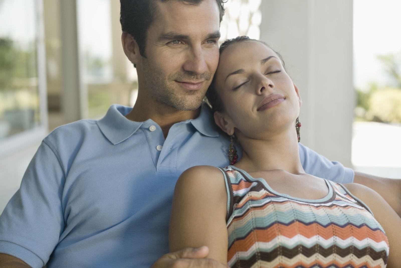 young woman leaning on the man's shoulder while closing her eyes inside a resort house