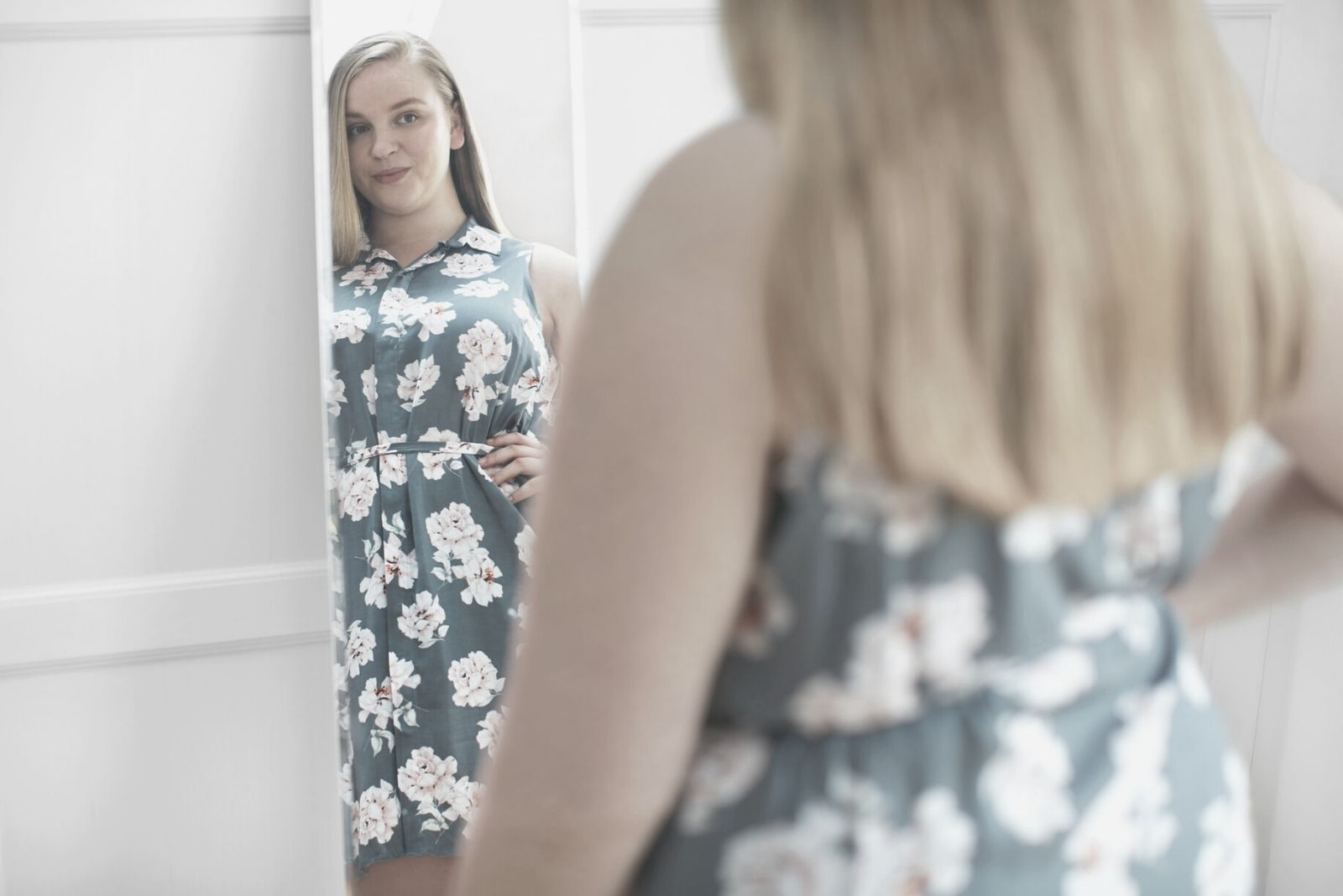 young woman looking at her body smiling at the mirror wearing floral dress