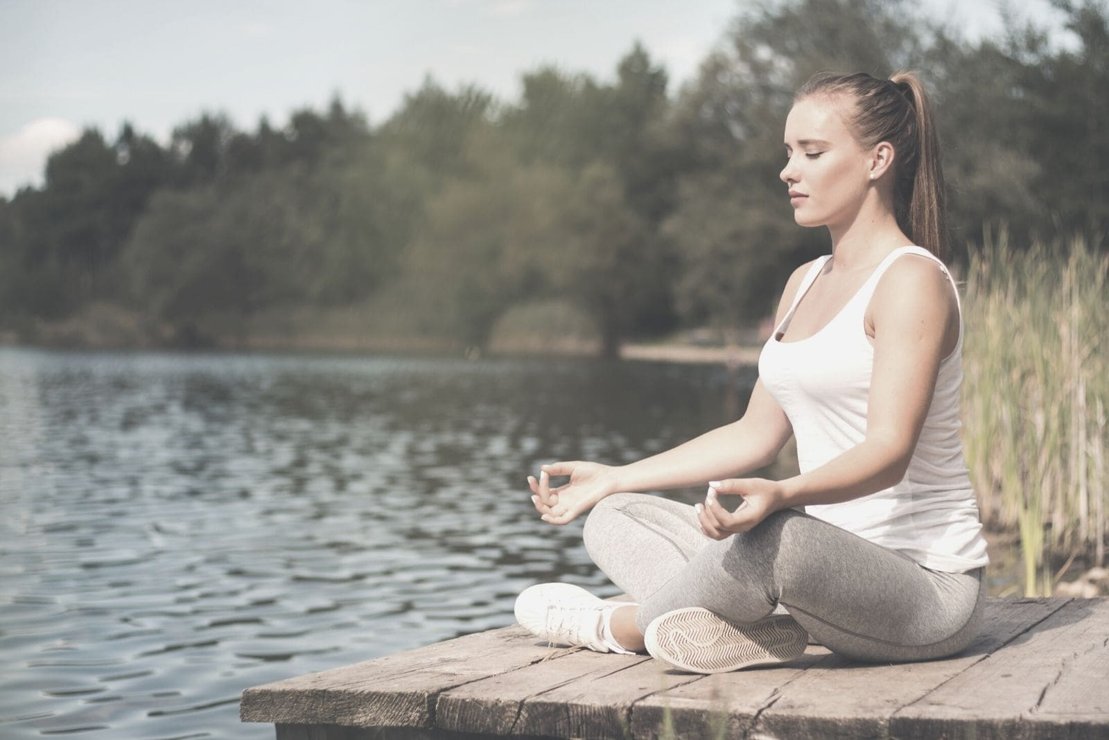 young woman meditating in yoga pose on top of a wooden platform near the body of water