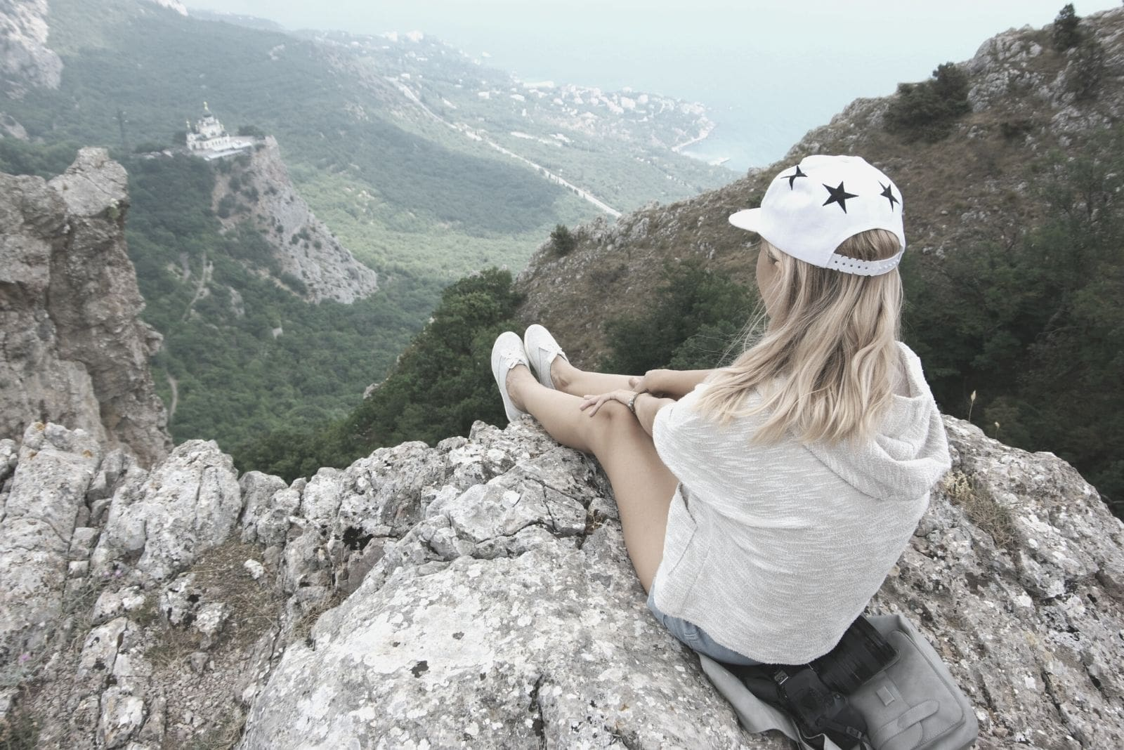 young woman on top of the mountain sitting and looking down below