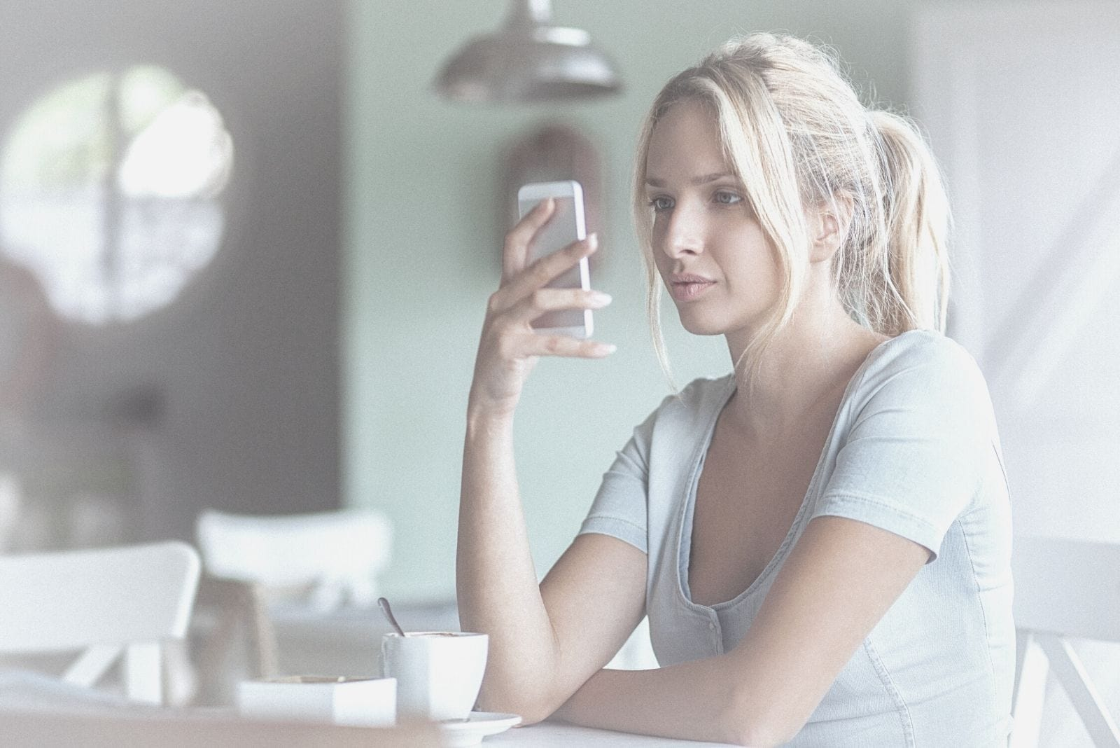 young woman texting pensively sitting inside a cafe