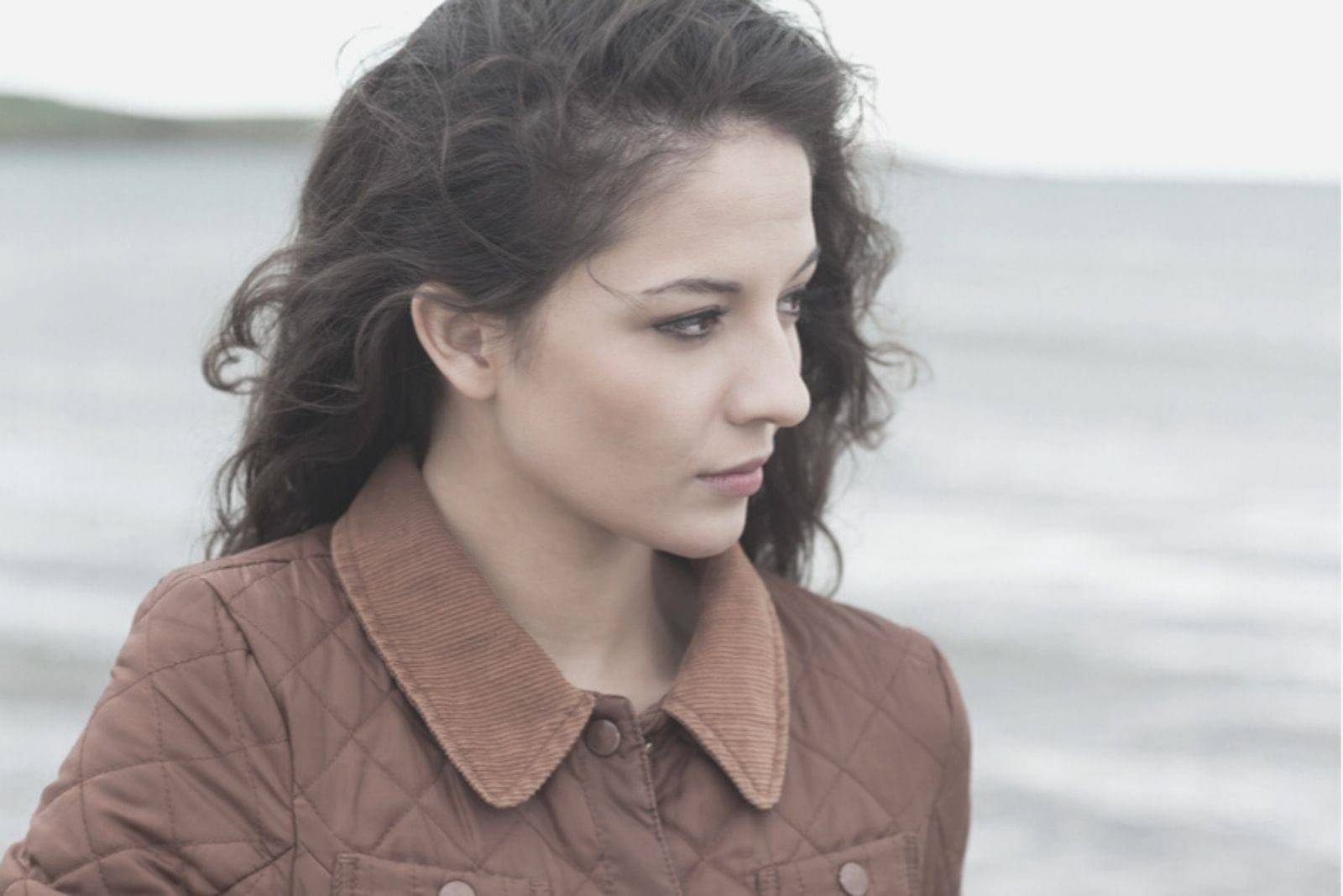 young woman thoughtful and looking at the sea wearing coat in close up image
