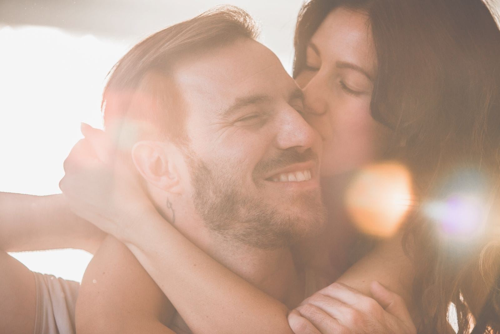 woman kissing and hugging her happy and smiling boyfriend in close up image