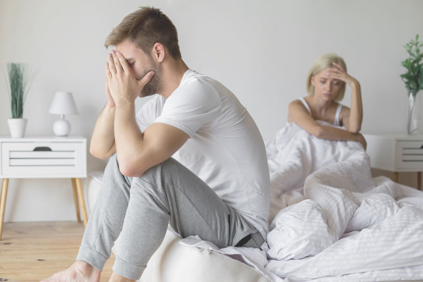 couple having a family problem sitting in bed trying to resolve inside the bedroom