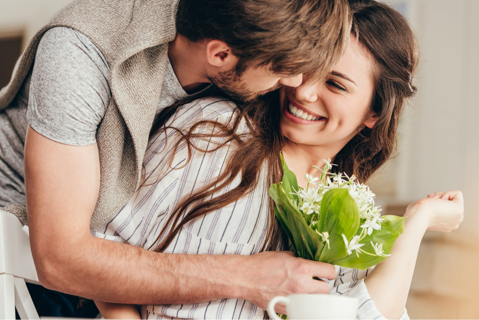 a man hugged a woman and bought her a bouquet of flowers