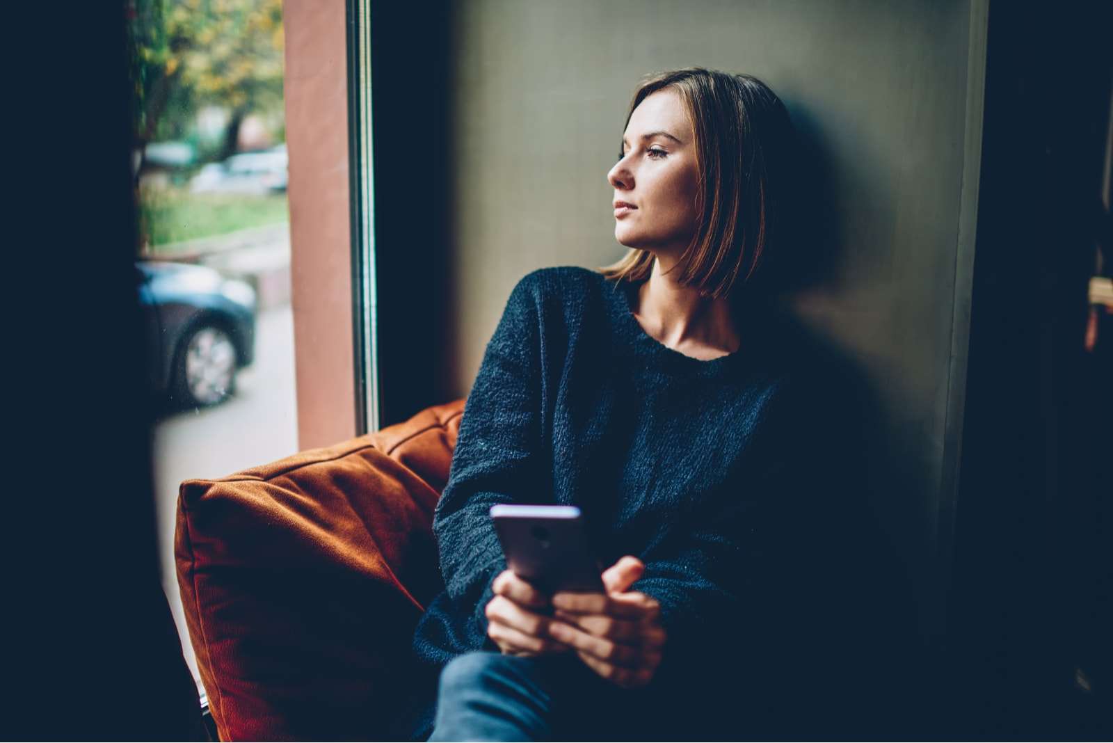 Woman dressed in black casual outfit looking out the window