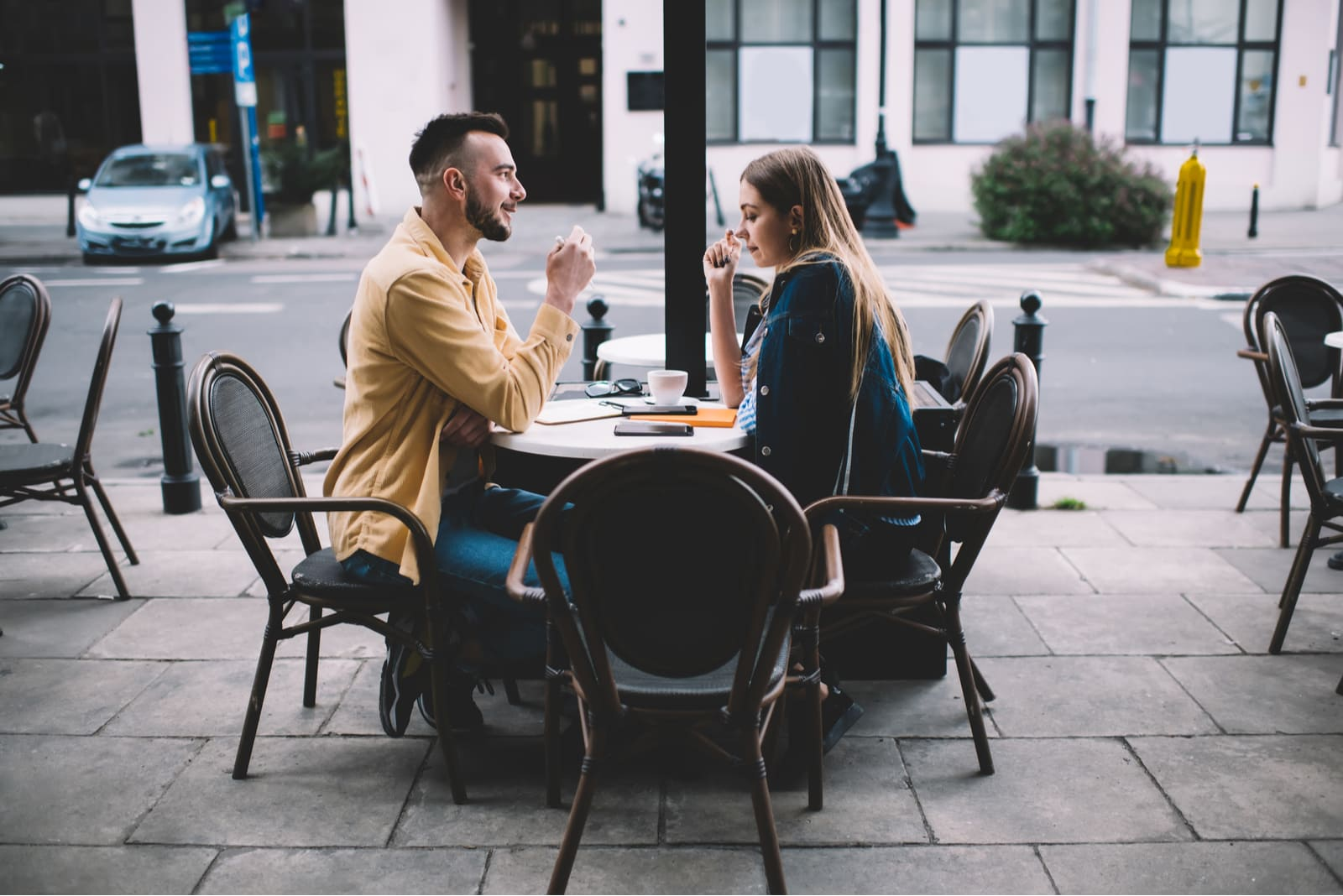 a couple on a cafe terrace drinking coffee and talking