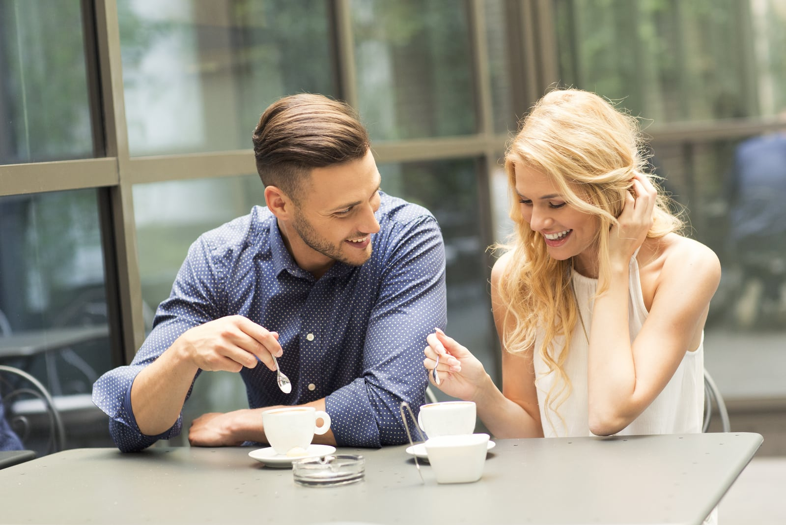 a man and a woman over coffee talking and laughing