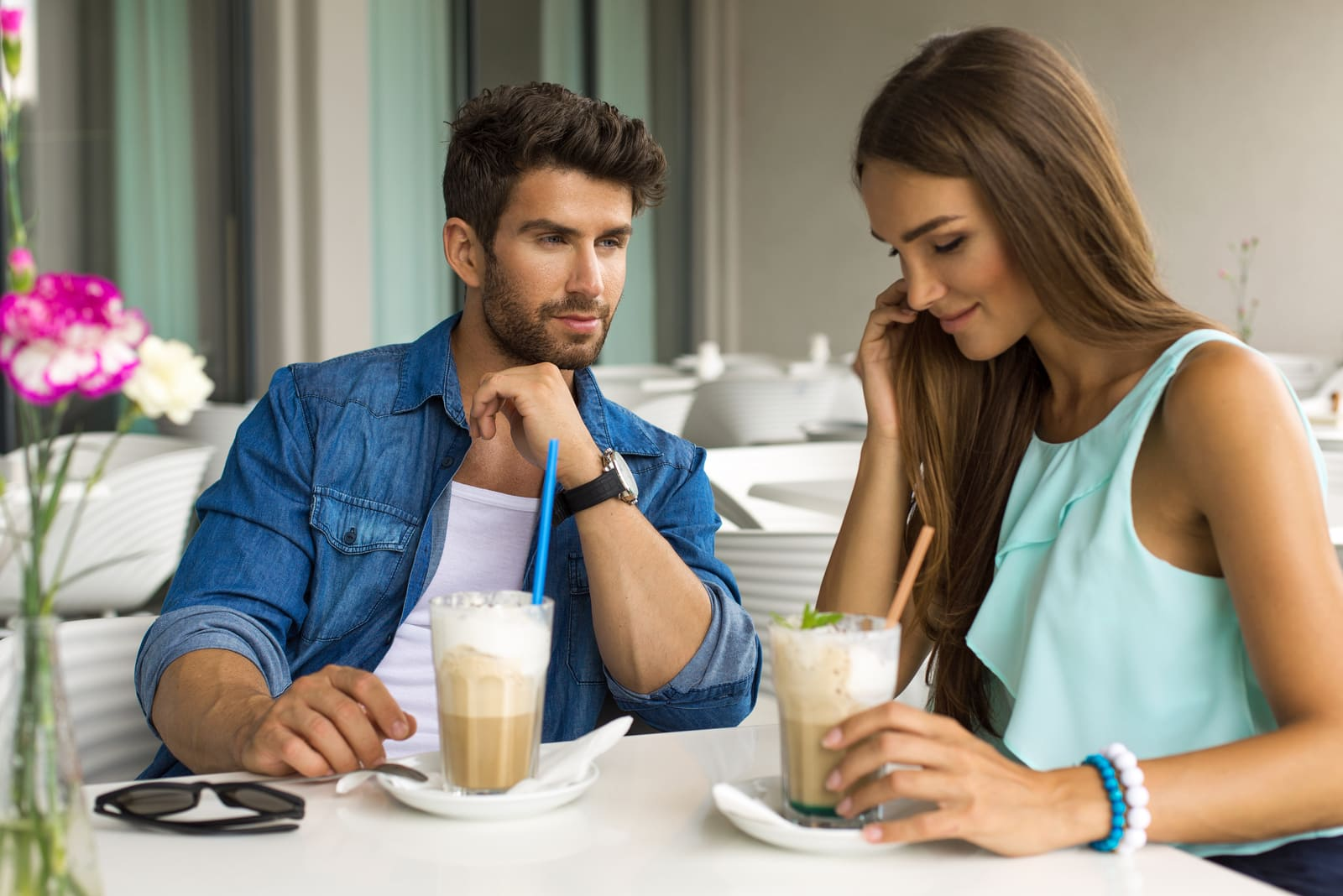 a man and a woman sit and drink hot chocolate