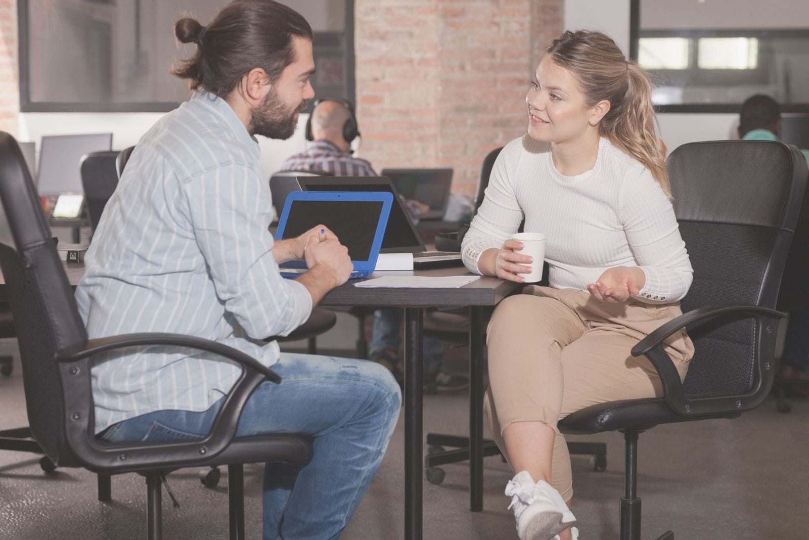 a man and woman talking in the office while having coffee break