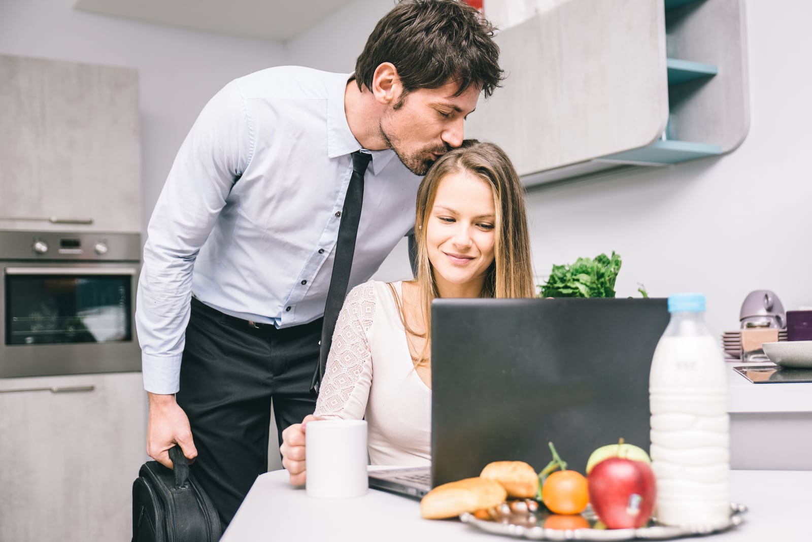 a man kisses a woman on the head while she sits behind a laptop