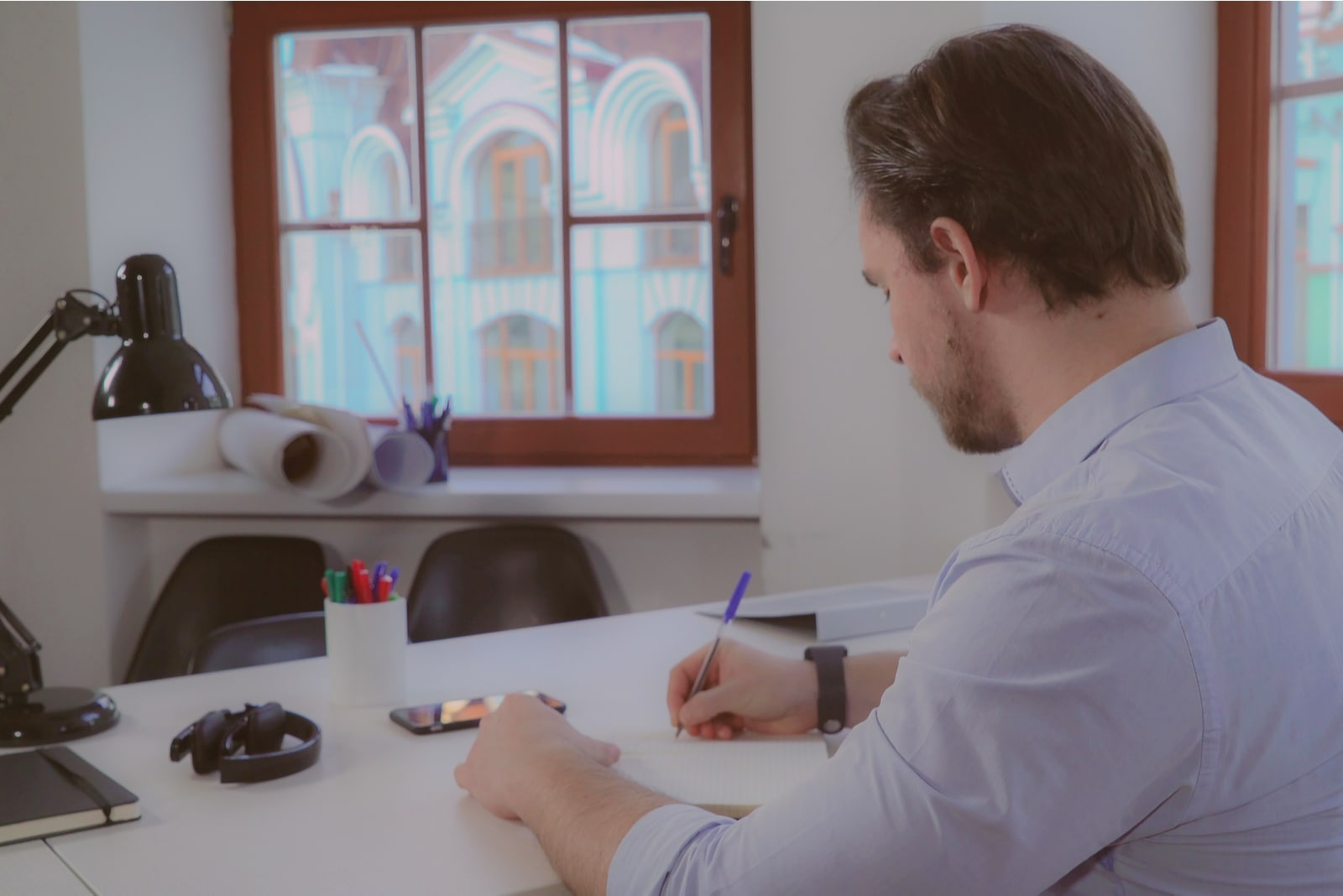 a man sits at a table and writes a letter