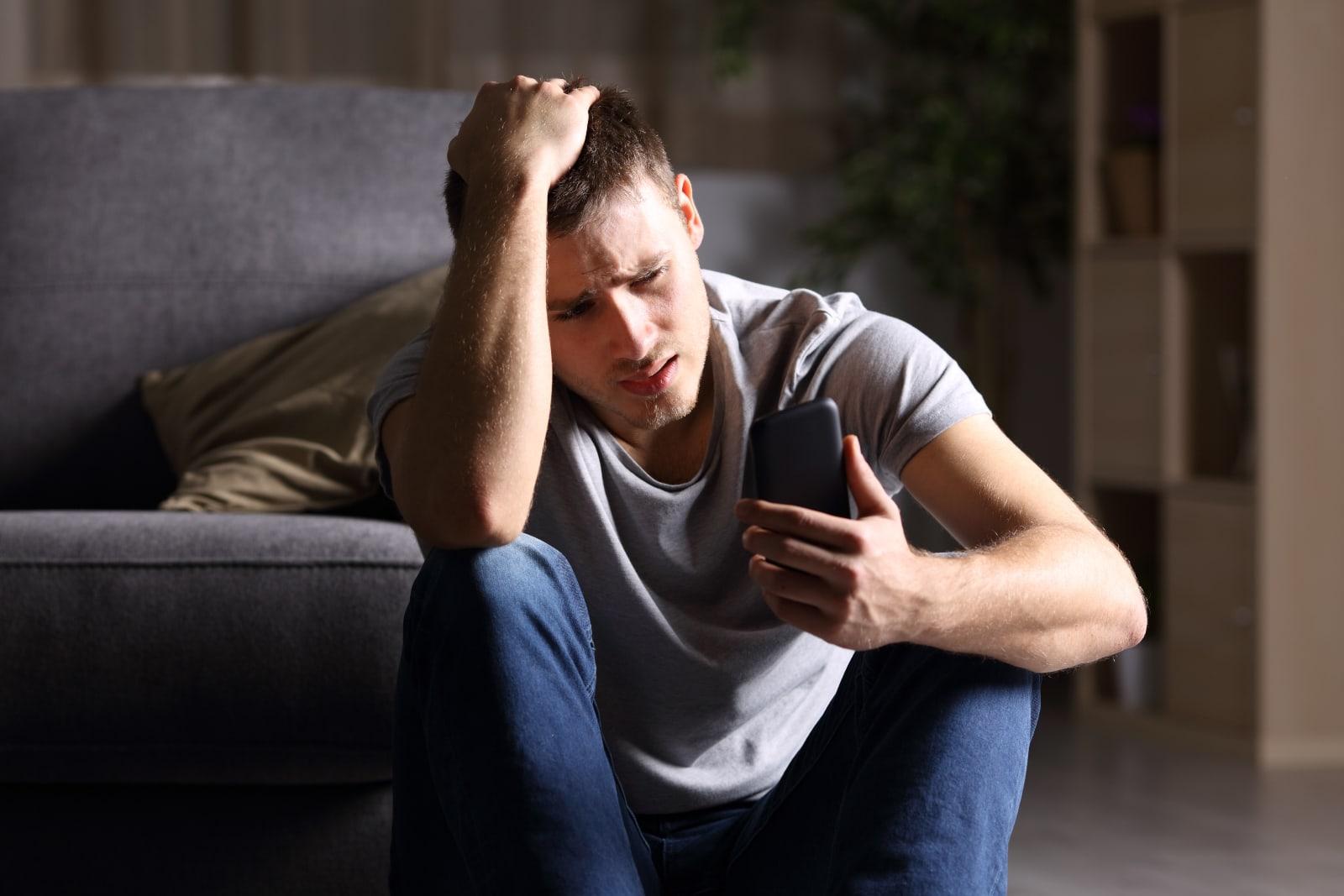 a sad man looking at his cell phone