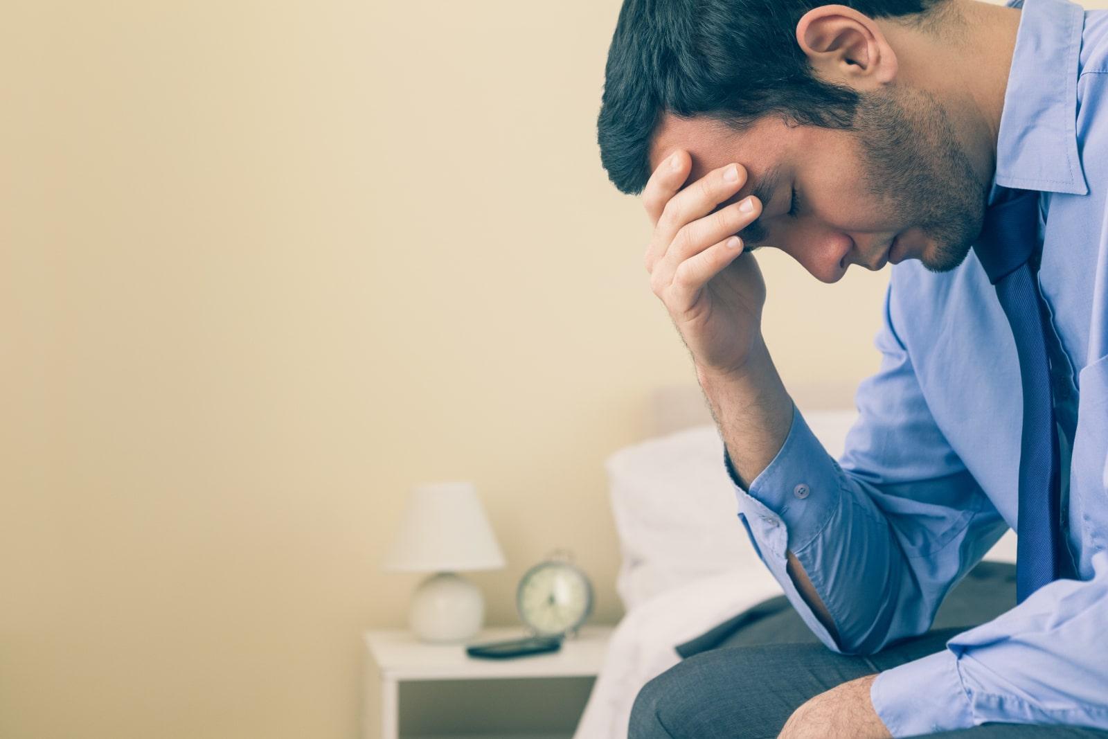a sad man who has a headache