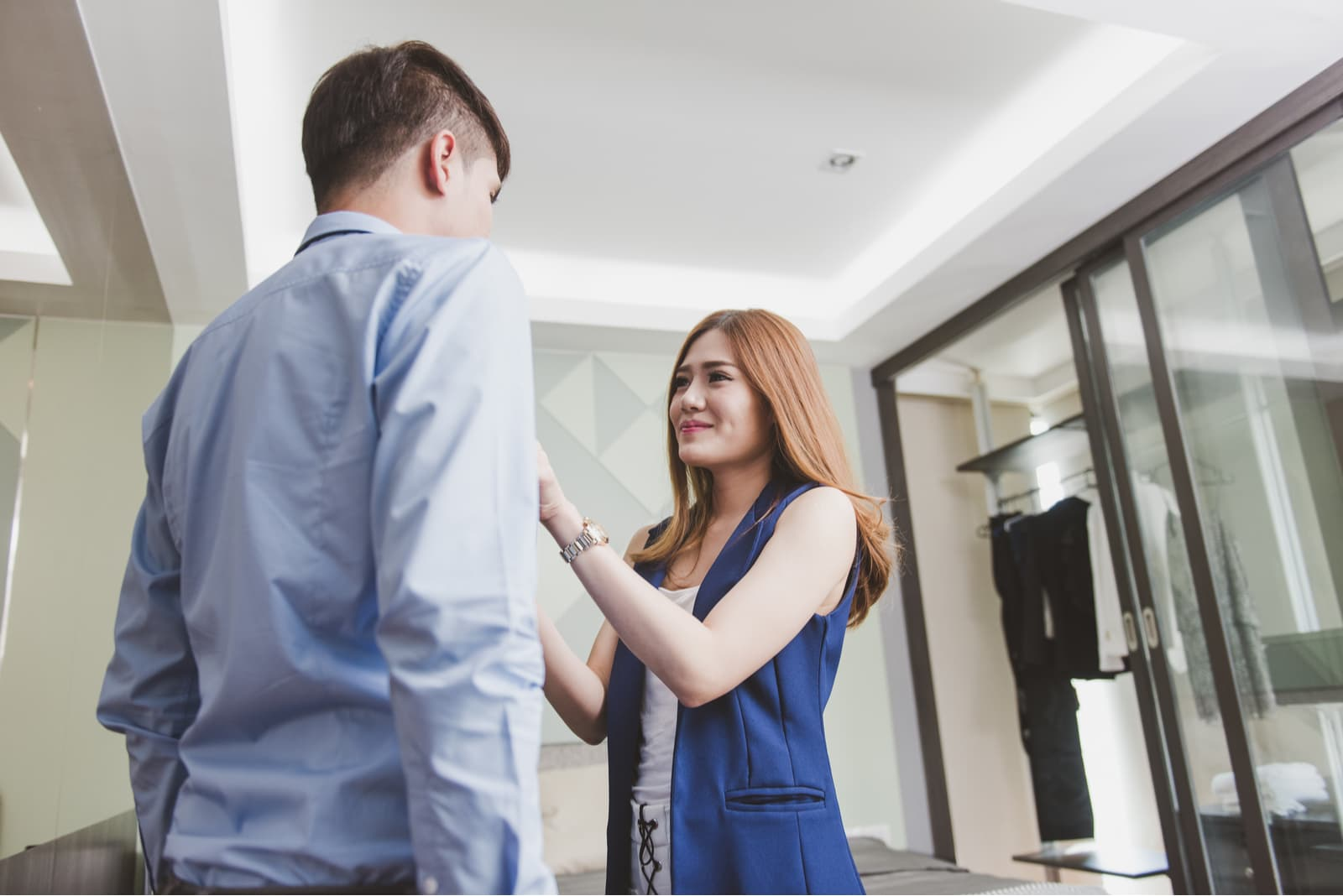 a smiling girl ties a tie to her boyfriend