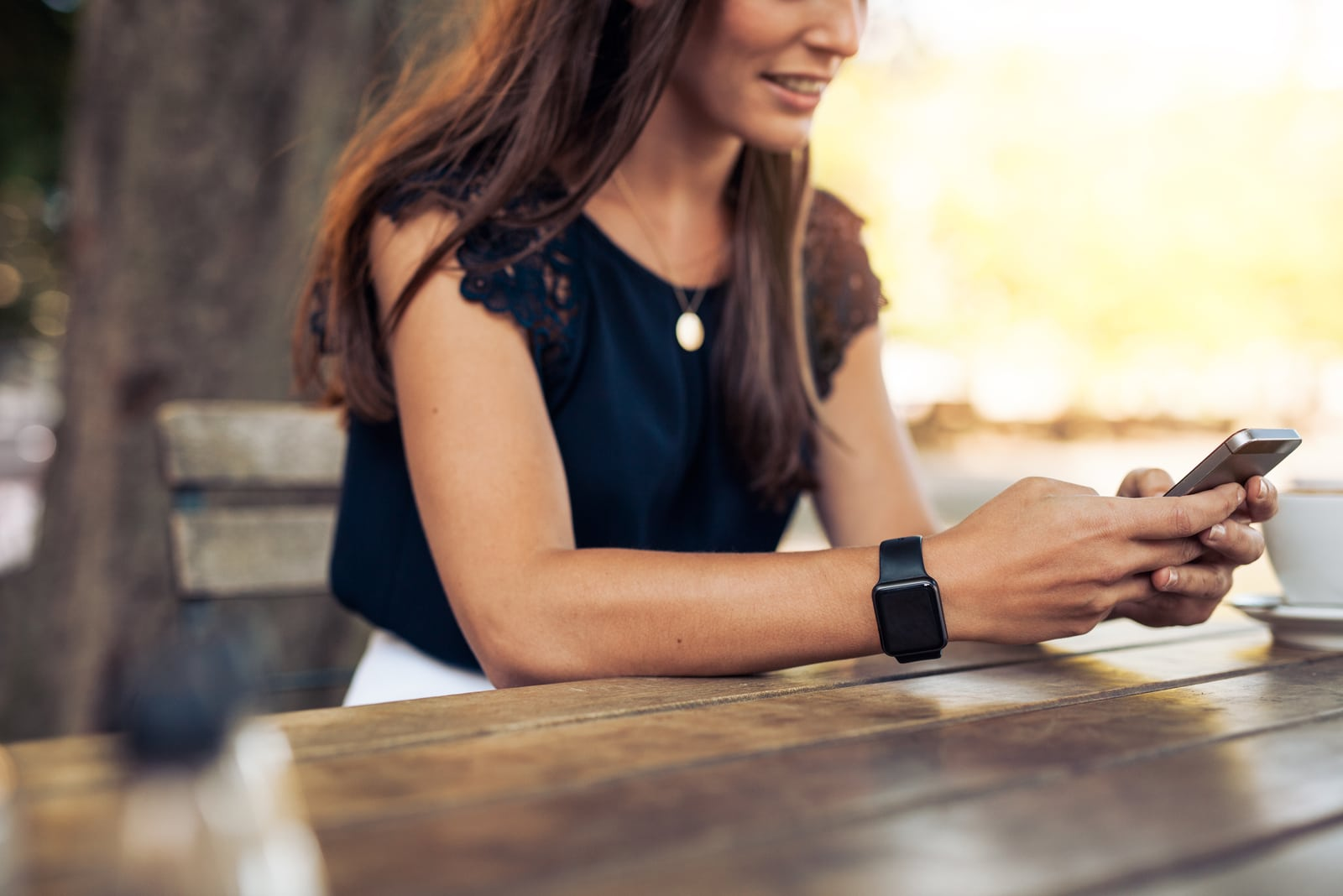 a woman sits at a table and a key on the phone