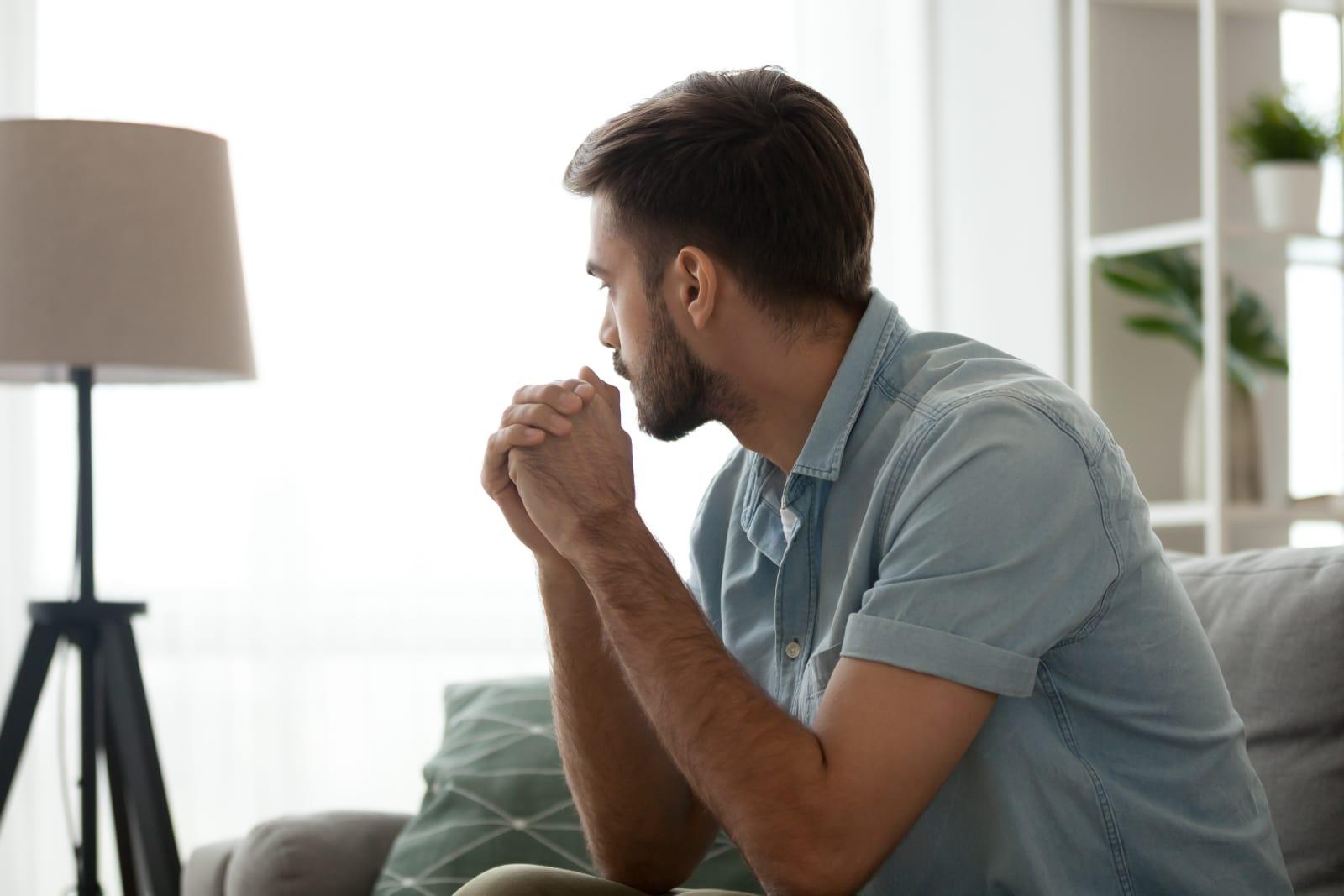 a worried man sits alone