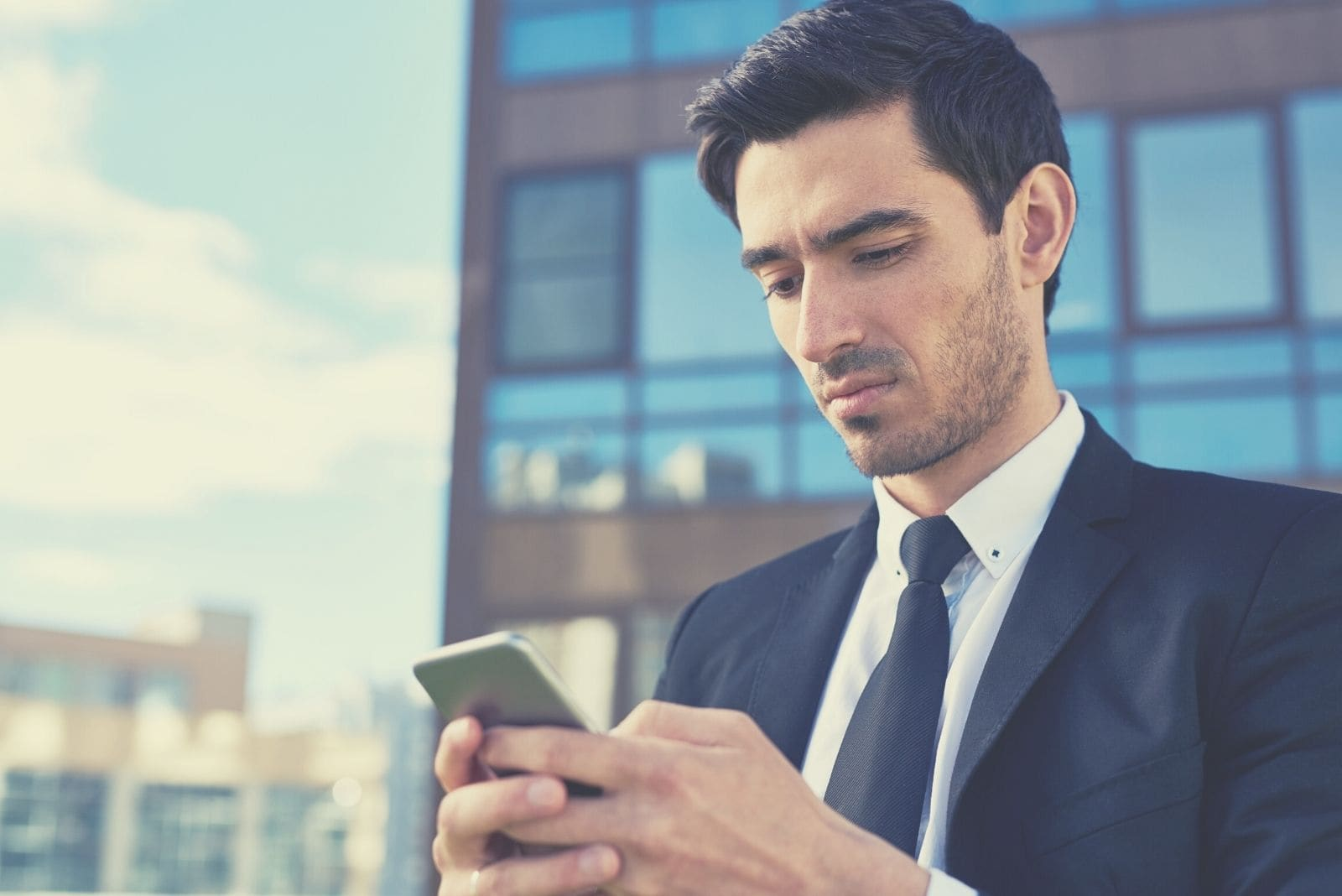 annoyed man answering text message from his smartphone wearing business wear standing outside the office building