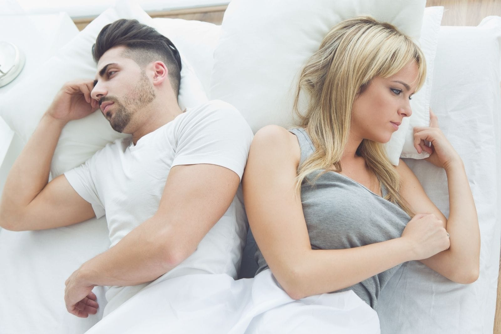 arguing couple in bed facing away from each other
