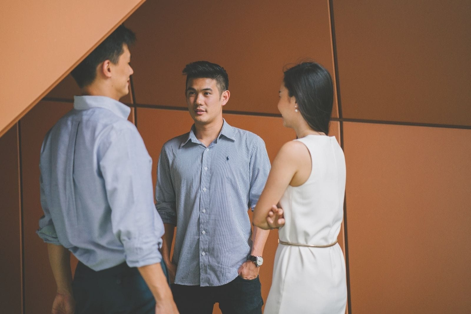 asian business people talking in the corner of the office standing