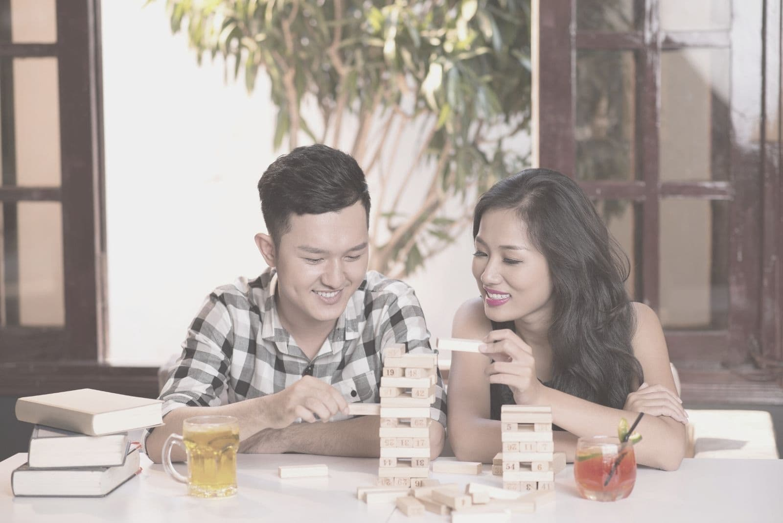 asian couple playing jenga game indoors with drinks on the side