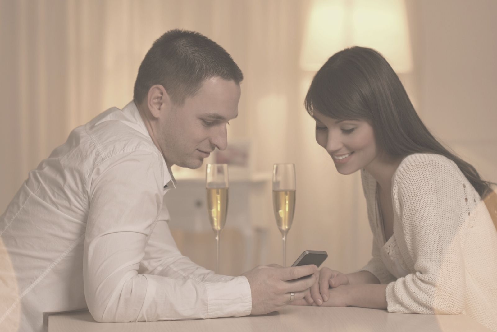 beautiful couple looking at the phone during their wine date night